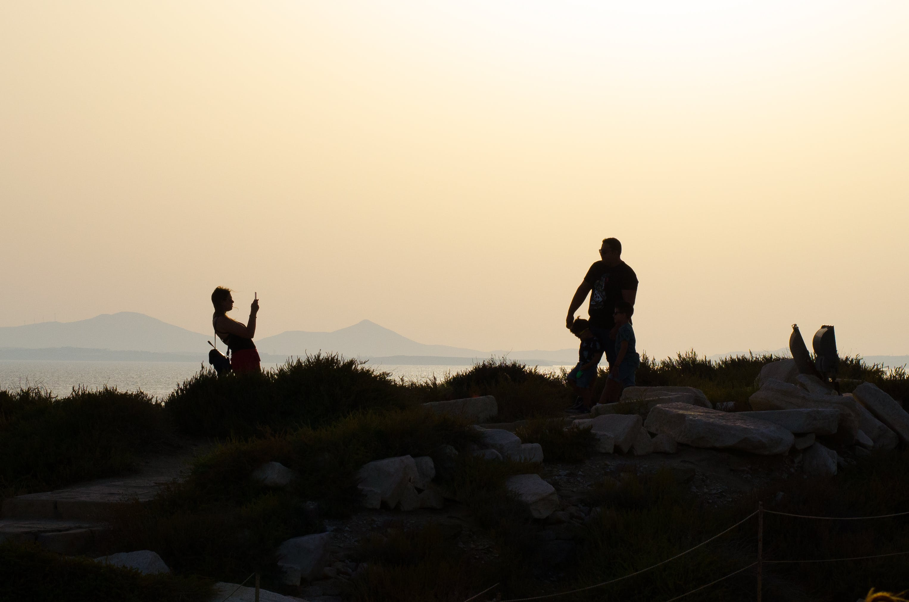 Silhouette Photo of Woman About to Take Picture of Man Standing on Green Grass during Golden Hour