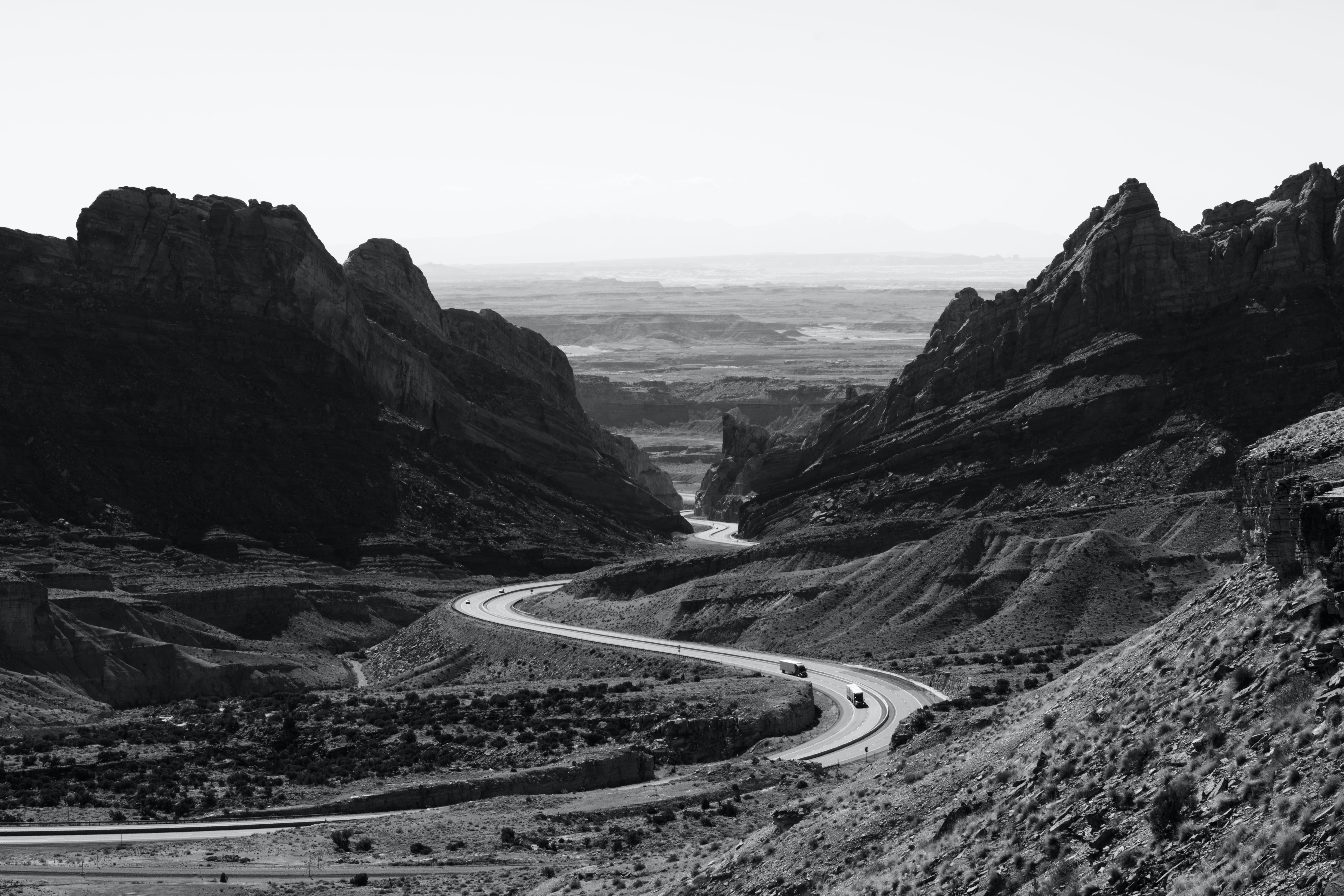 Grayscale Photo of Roadway Surrounded With Rocky Mountains