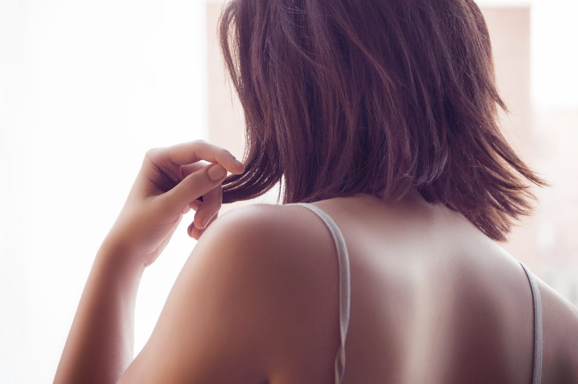 Lady Wearing White Spaghetti Strap Top and Holding Her Brown Short Hair