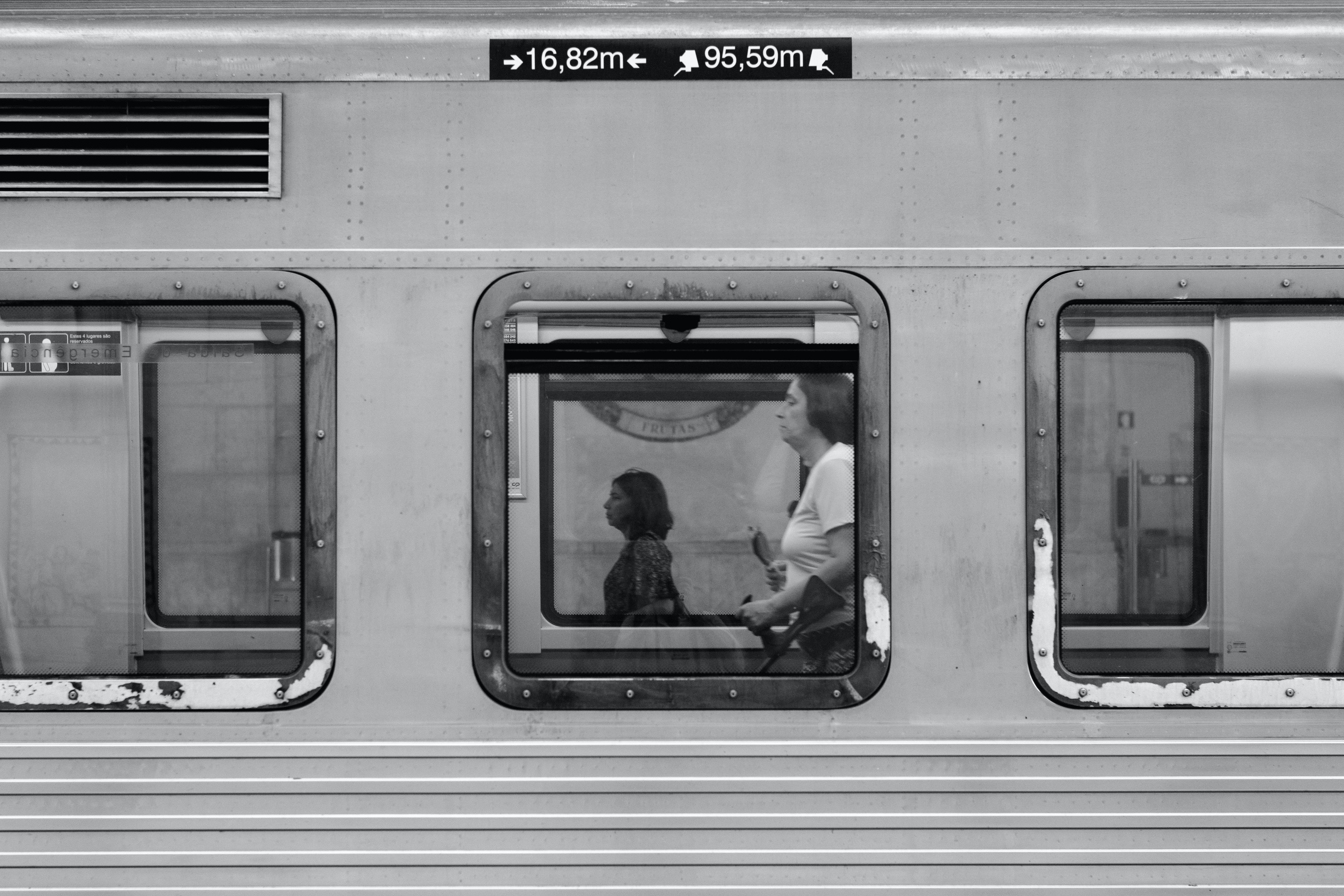 Grayscale Photography of Woman Standing Inside Train
