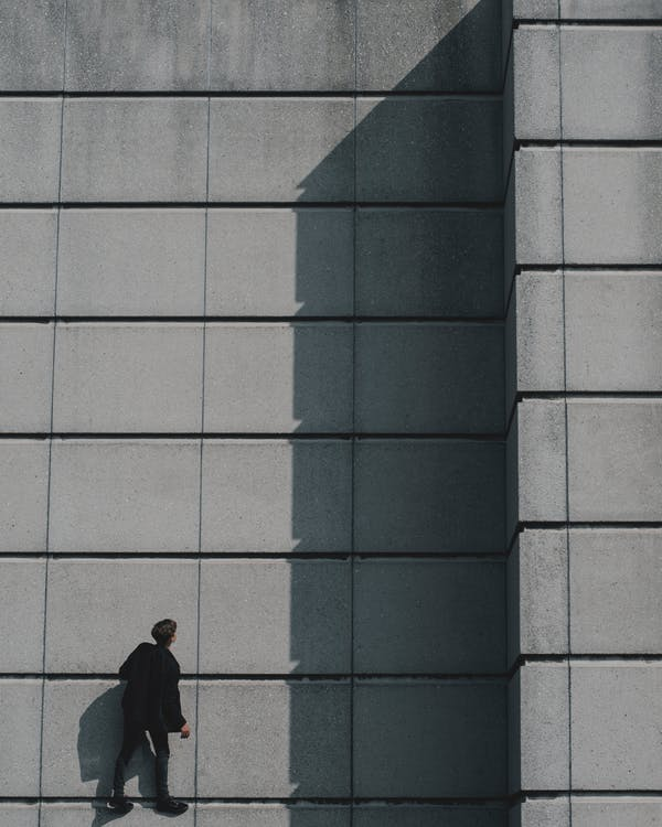 Photo of Man Standing on Concrete Building