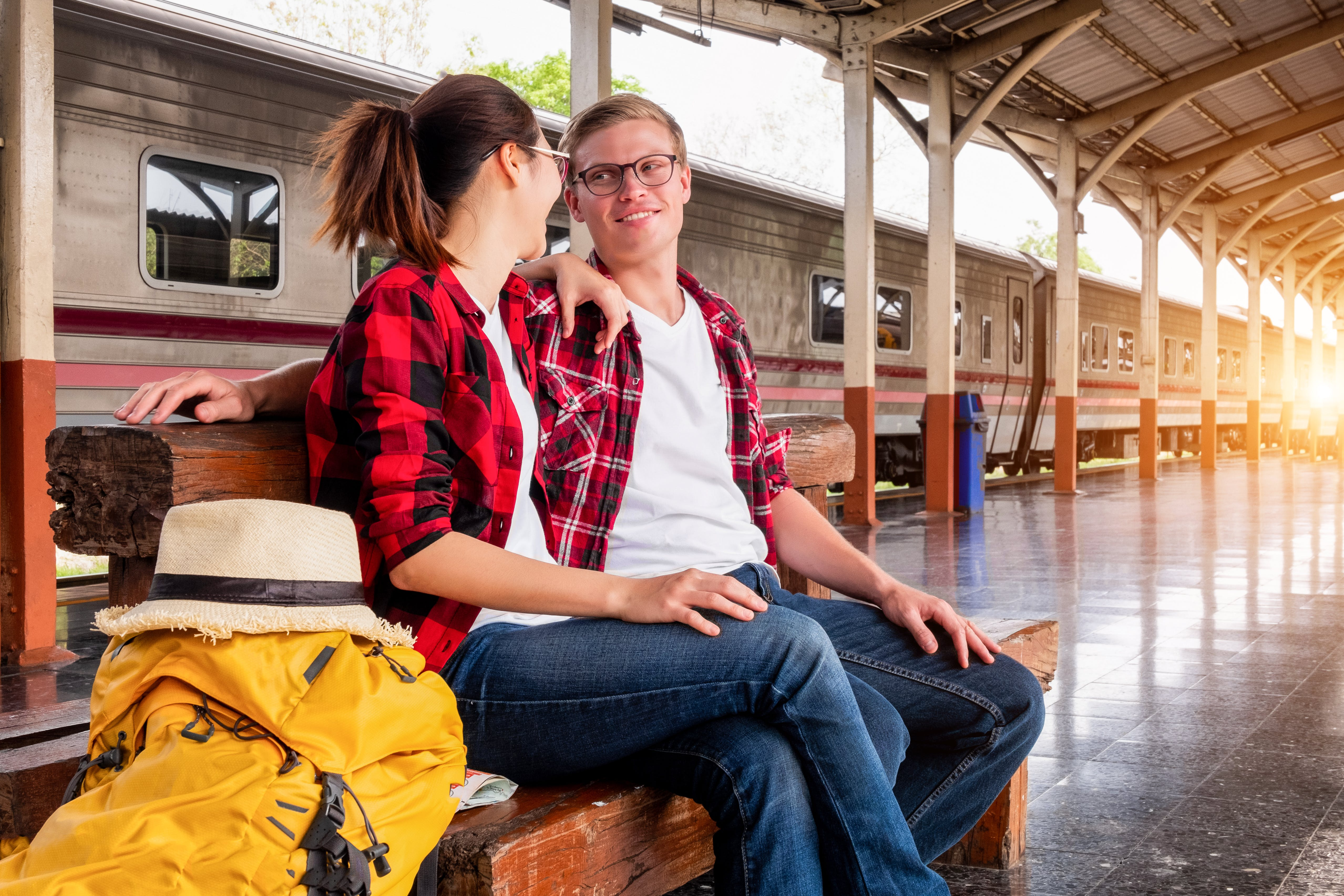 Man and Woman Sitting on Brown Wooden Bench at the Train Station