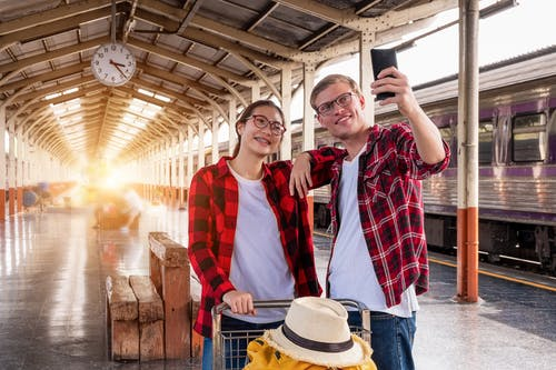 Man and Woman at the Train Station Taking a Selfie