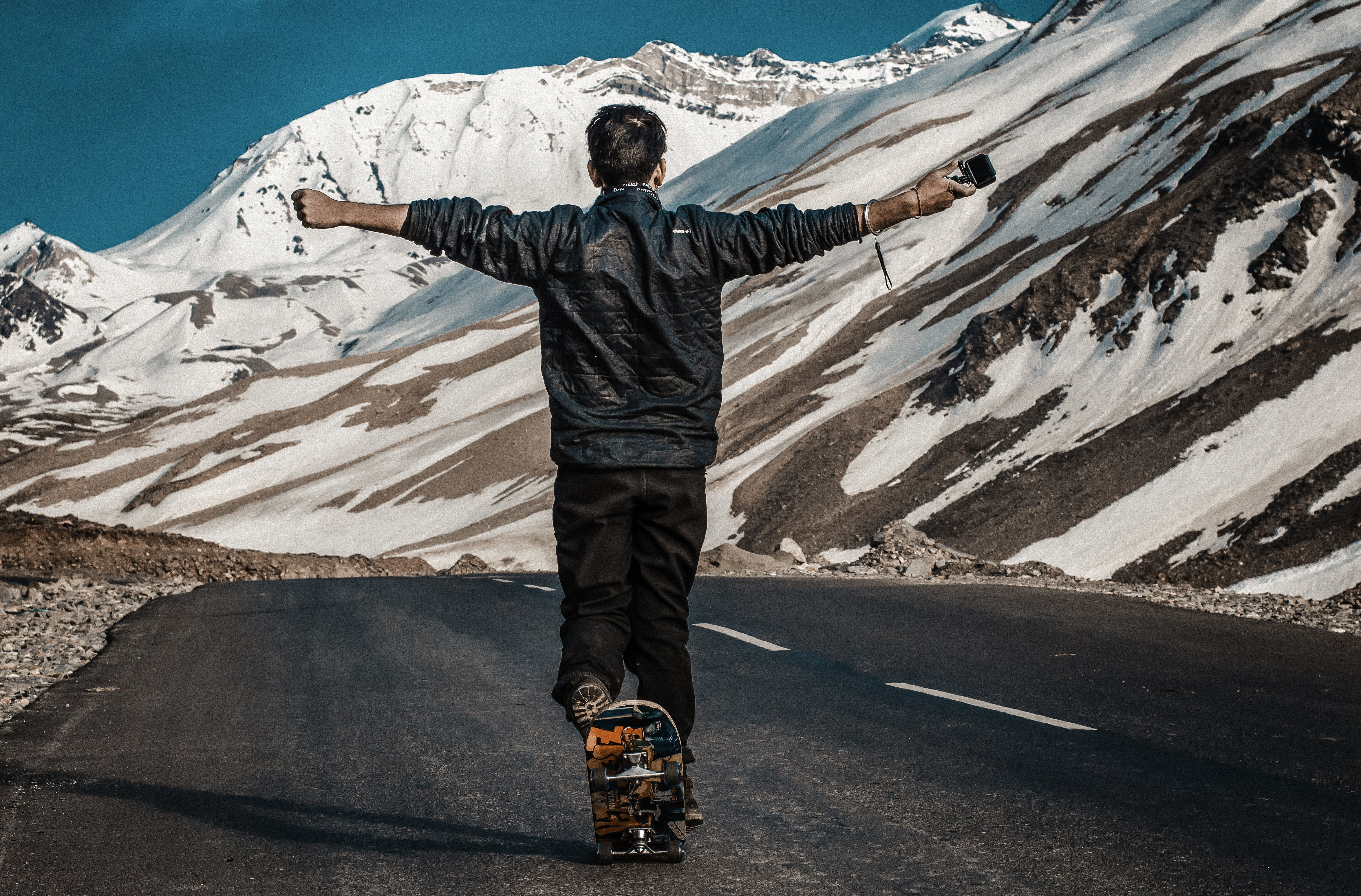 Photo of a Man I the Middle of Road Using Skateboard