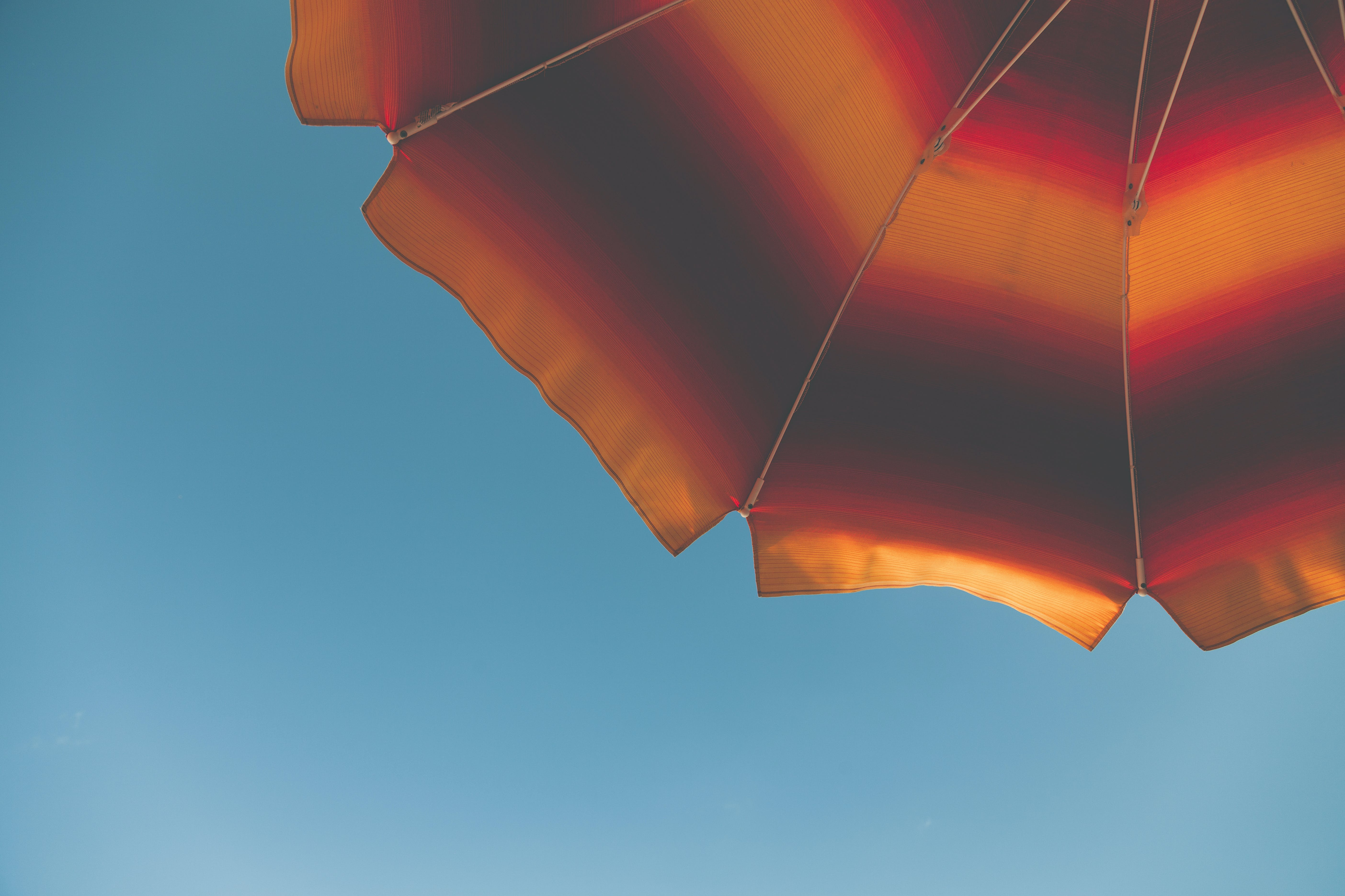 Low Angle Photography of Black and Orange Beach Umbrella
