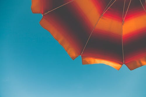 Low Angle Photography of Black and Orange Beach Umbrella