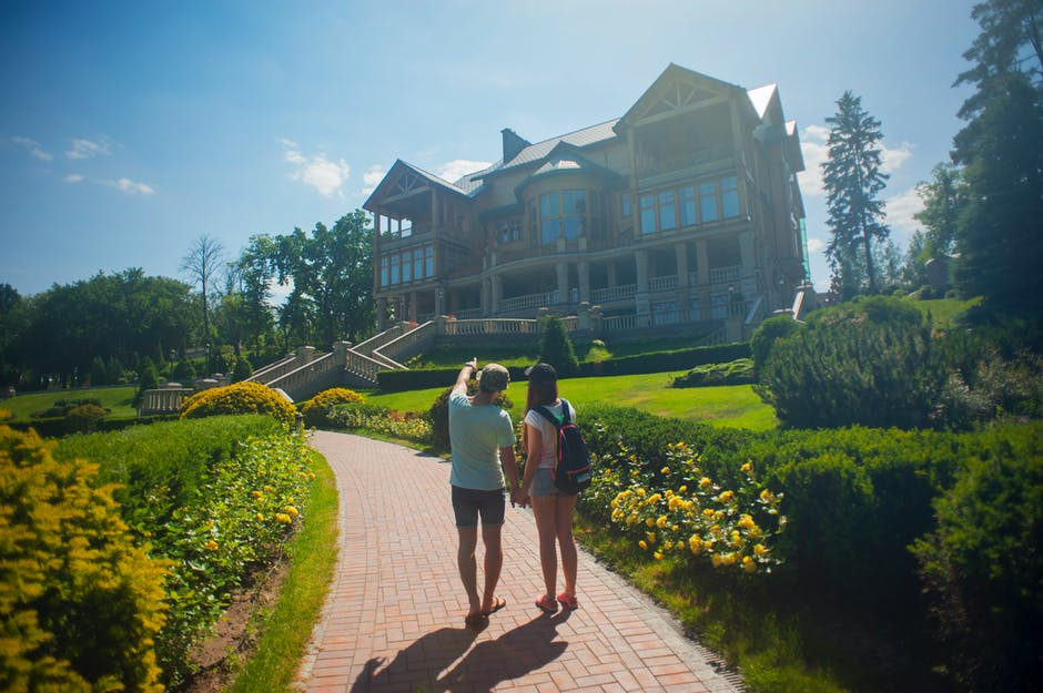 Photo of Couple Standing Outside the House