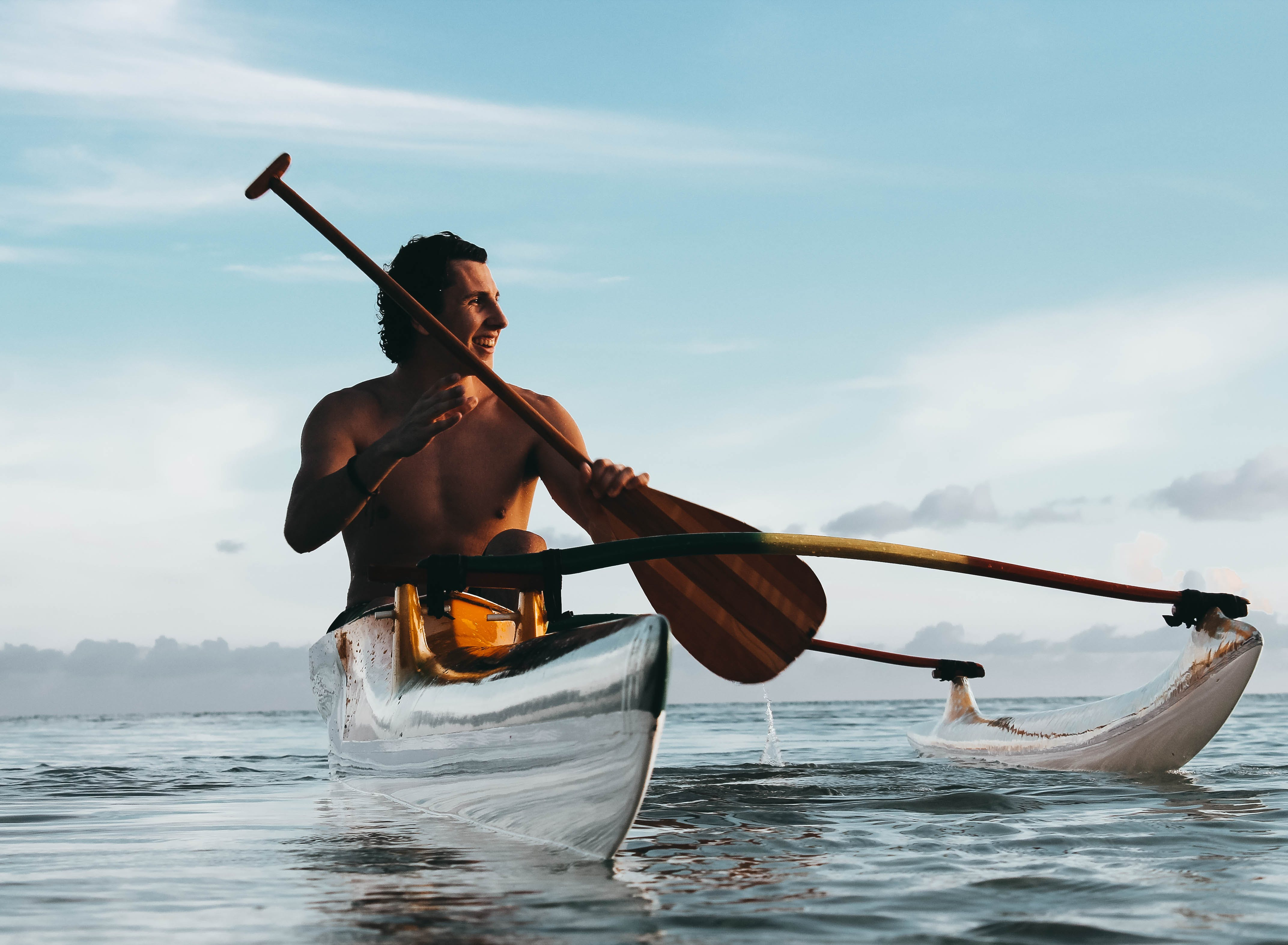 Man Riding on Boat Holding Brown Paddle