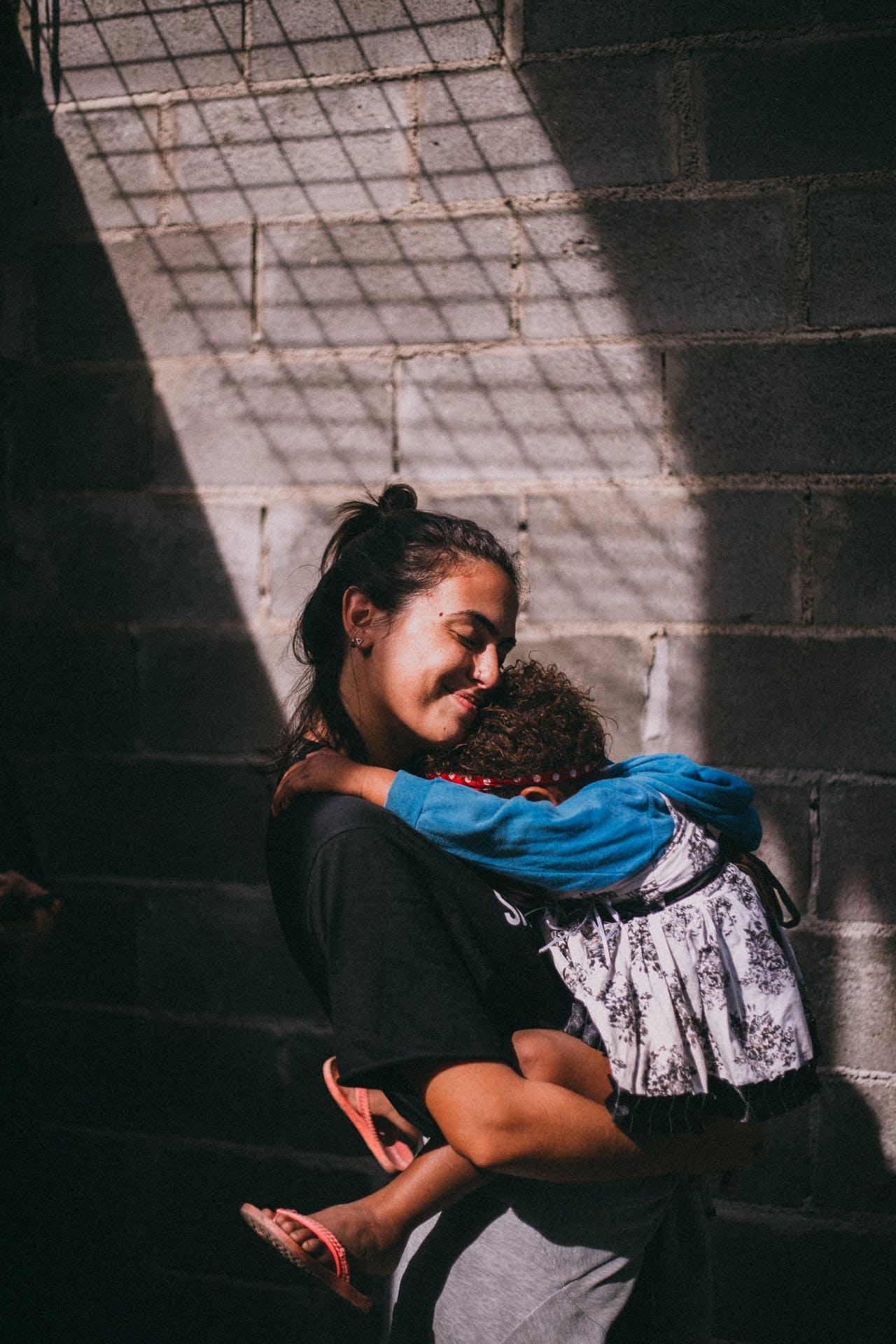 Woman Holding Girl Beside Gray Wall