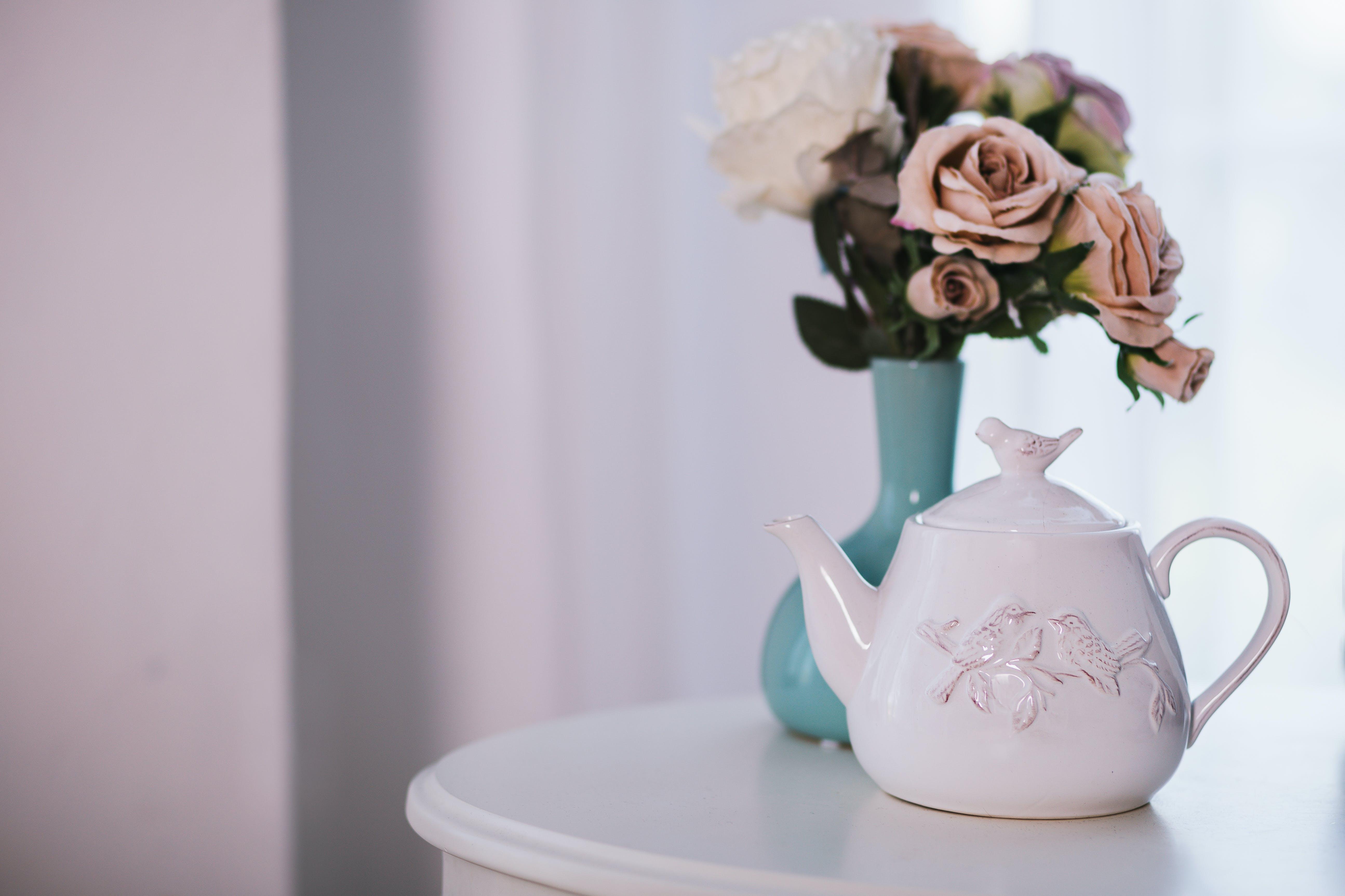 White Ceramic Teapot Near Flower Arrangement on White Surface