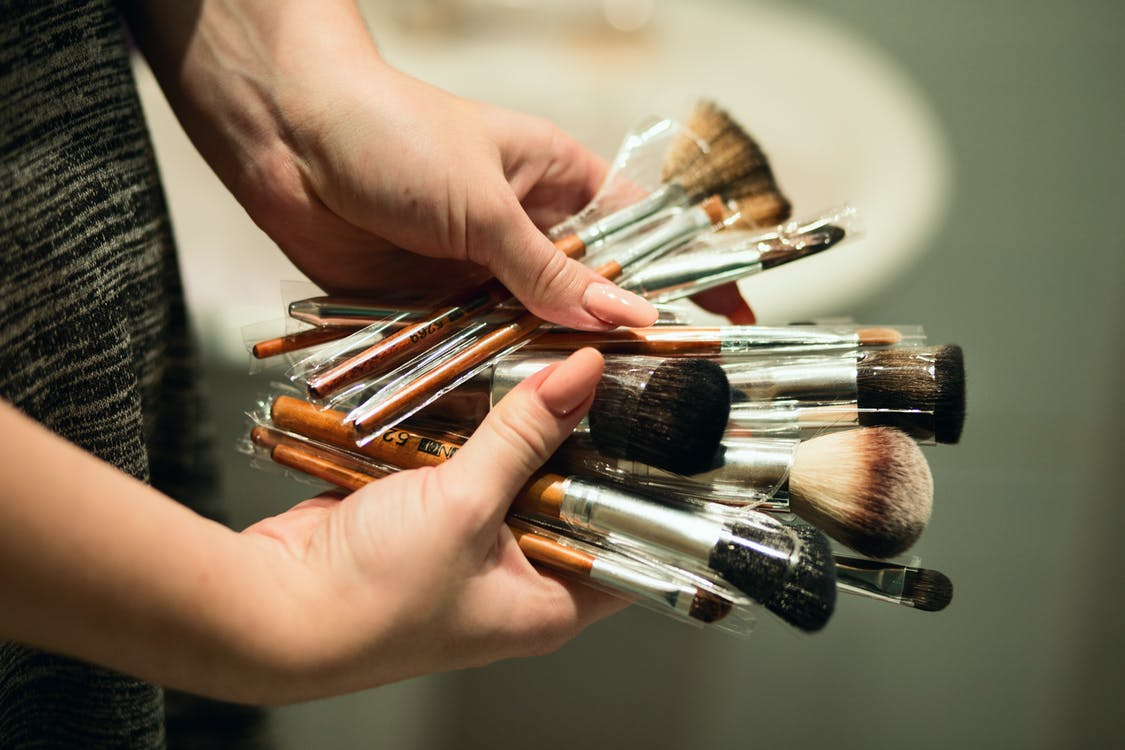Person Holding Makeup Brushes