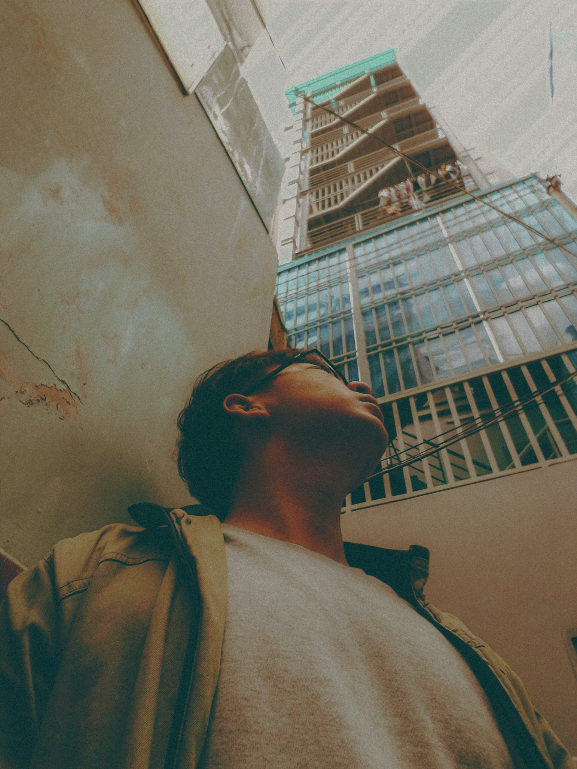 Man in Brown Jacket Looking up at a Tall Building