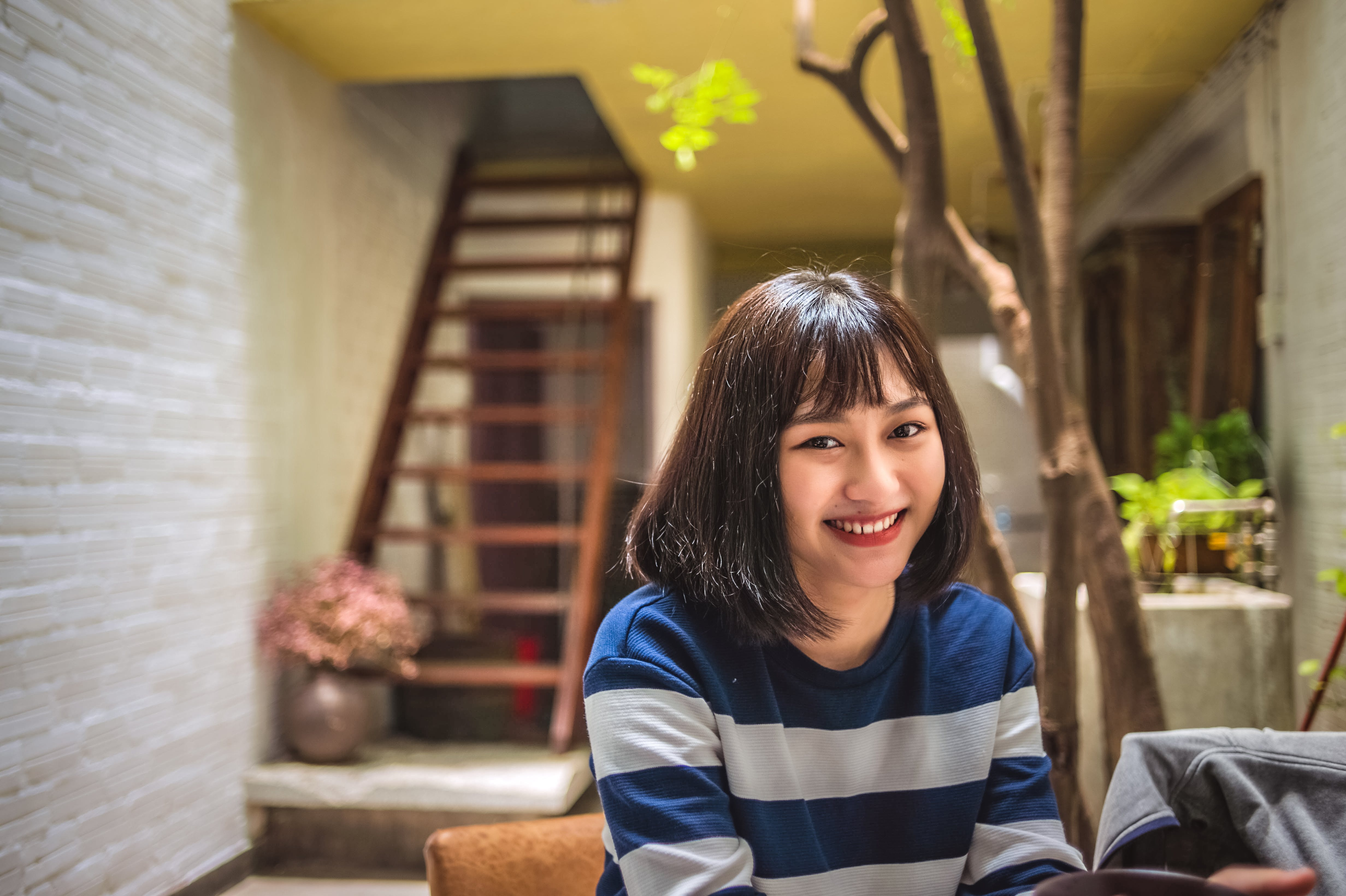 Smiling Woman in Blue and White Striped Shirt