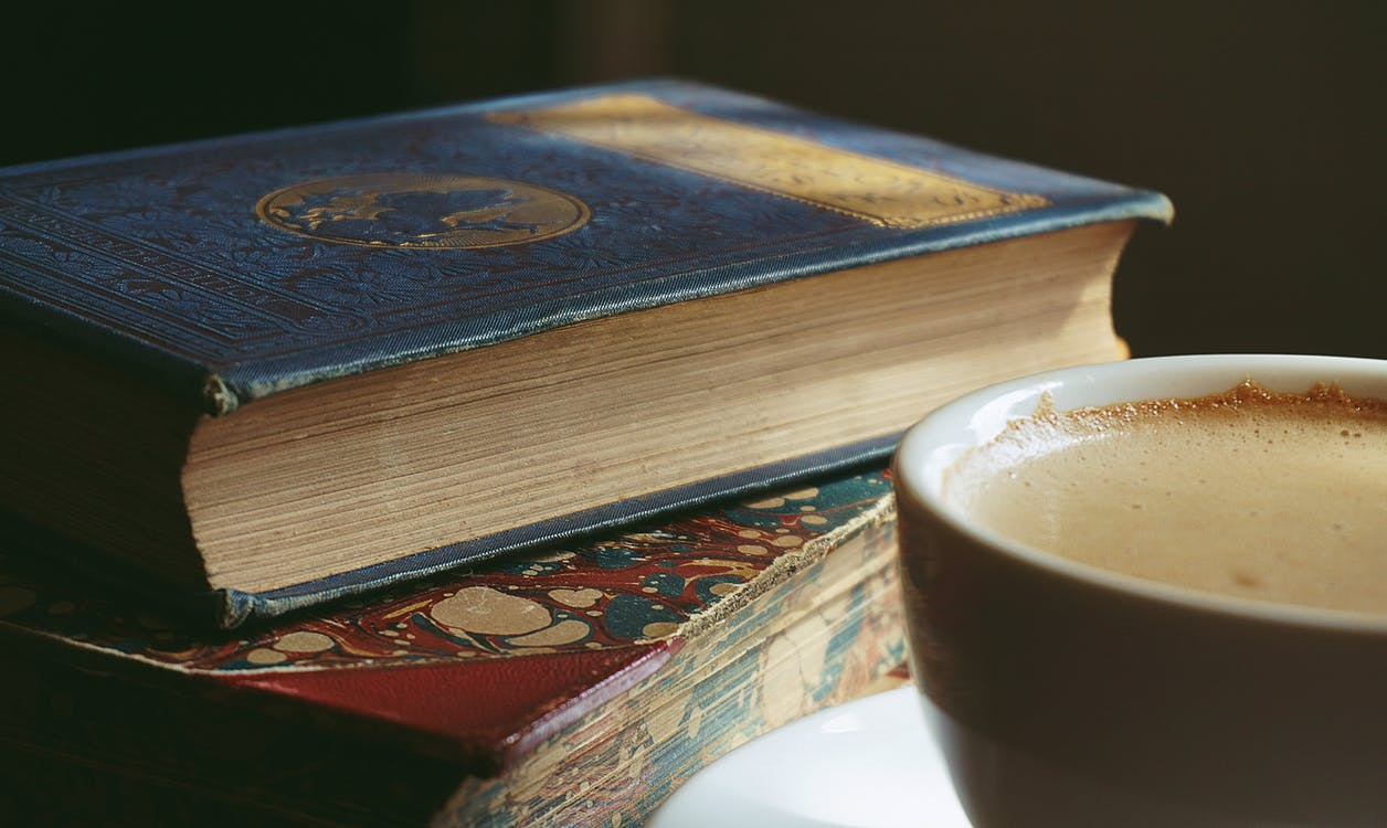 Book Beside Cup Filled With Brown Liquid