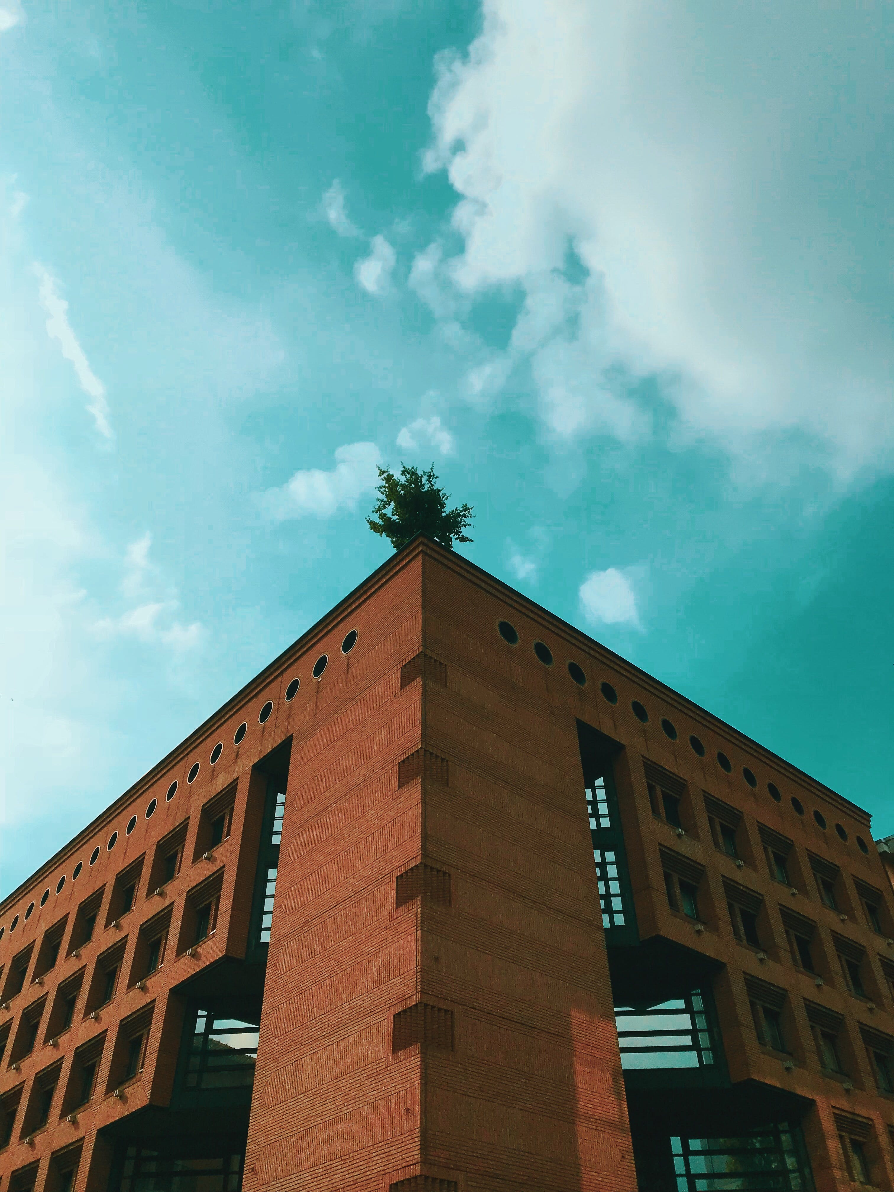 Brown Concrete Building Under Teal and White Cloudy Sky at Daytime