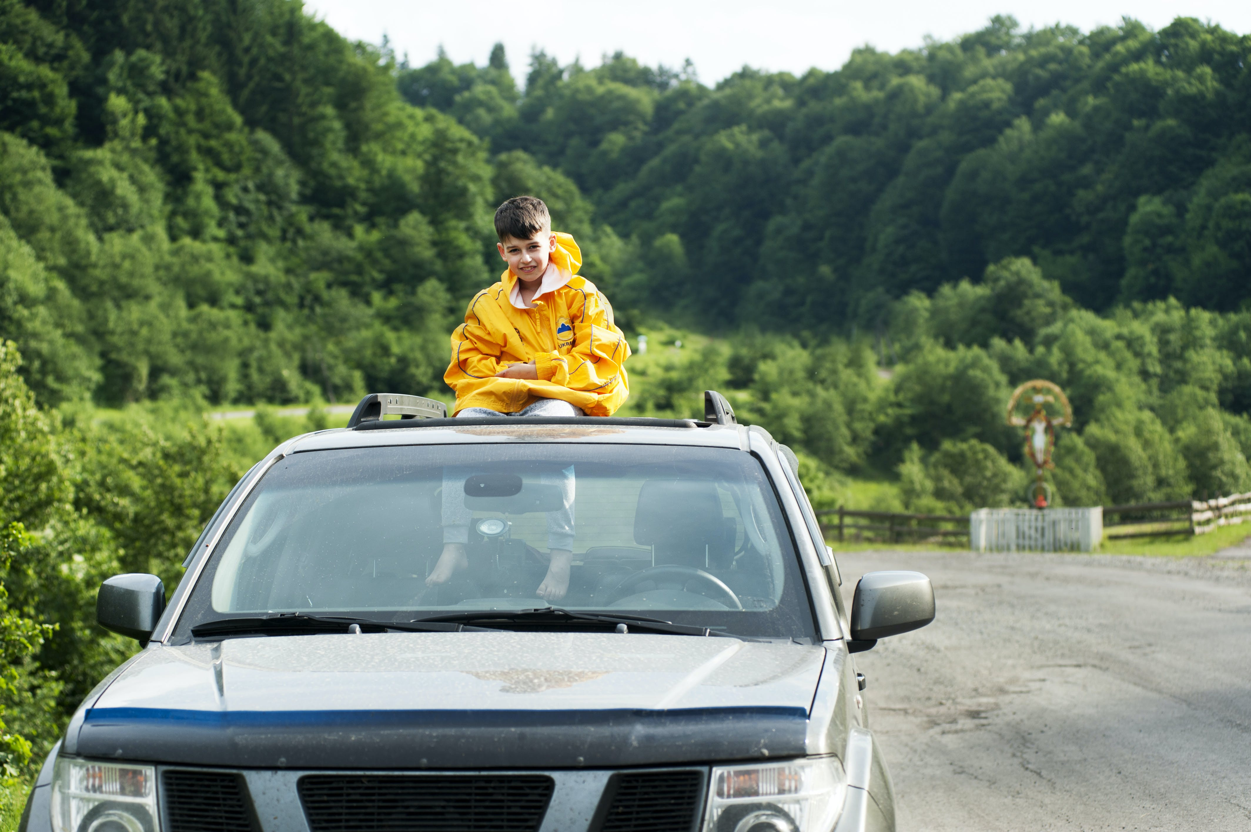 Child in Yellow Jacket Sitting on Roof of Nissan Frontier Through the Sunroof