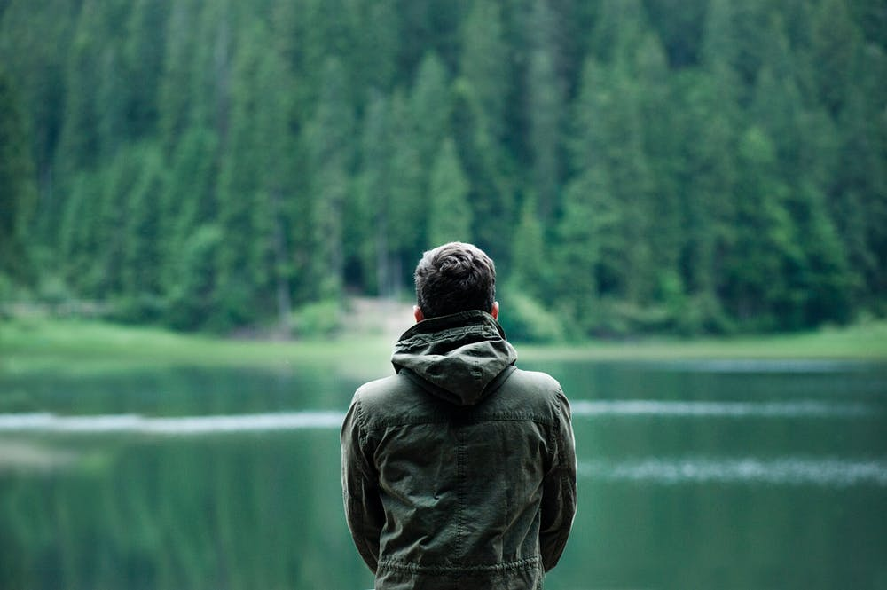 A man standing in front of a lake. | Photo: Pexels