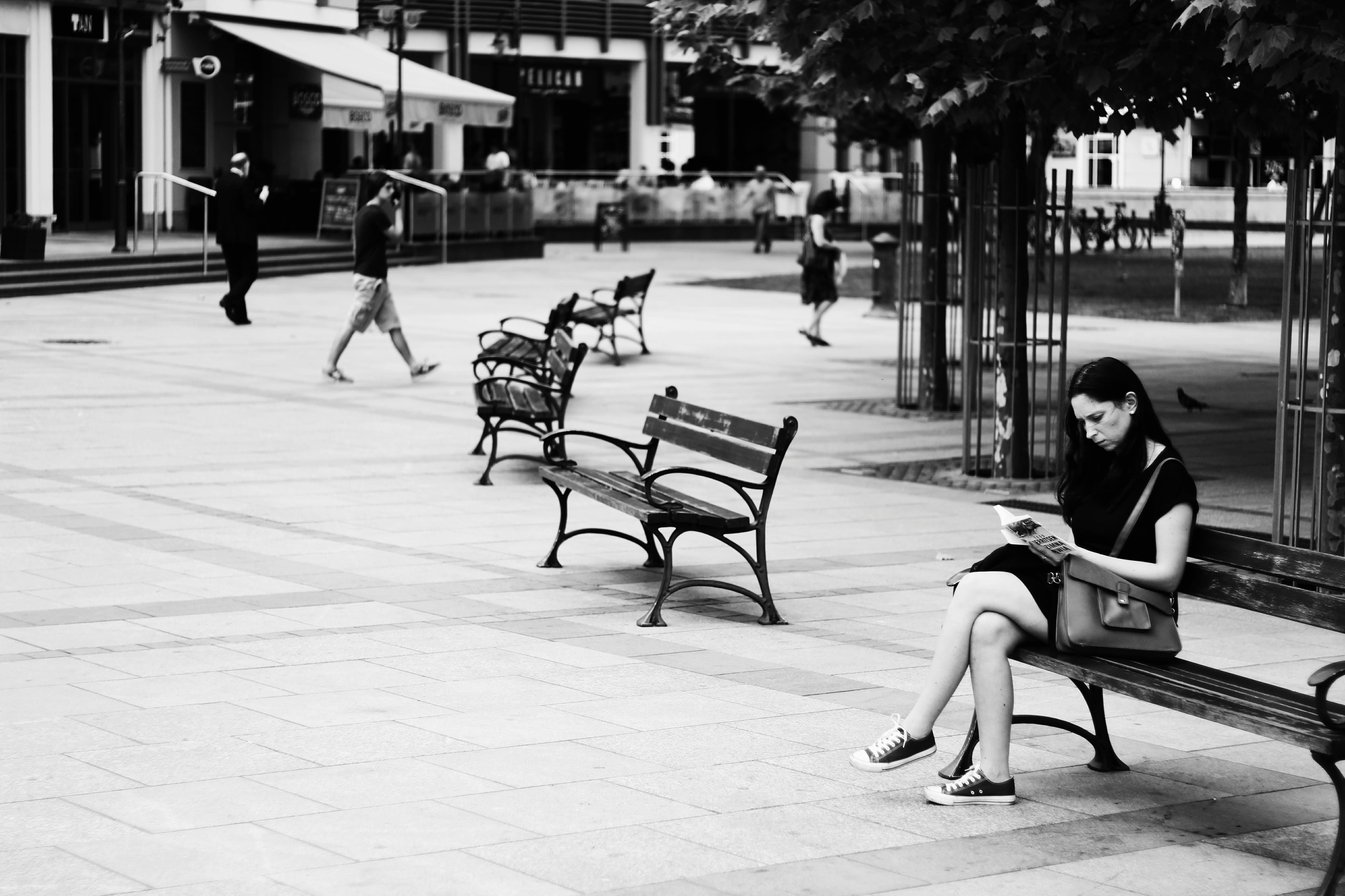 Grayscale Photography of Woman Sitting While Reading Book