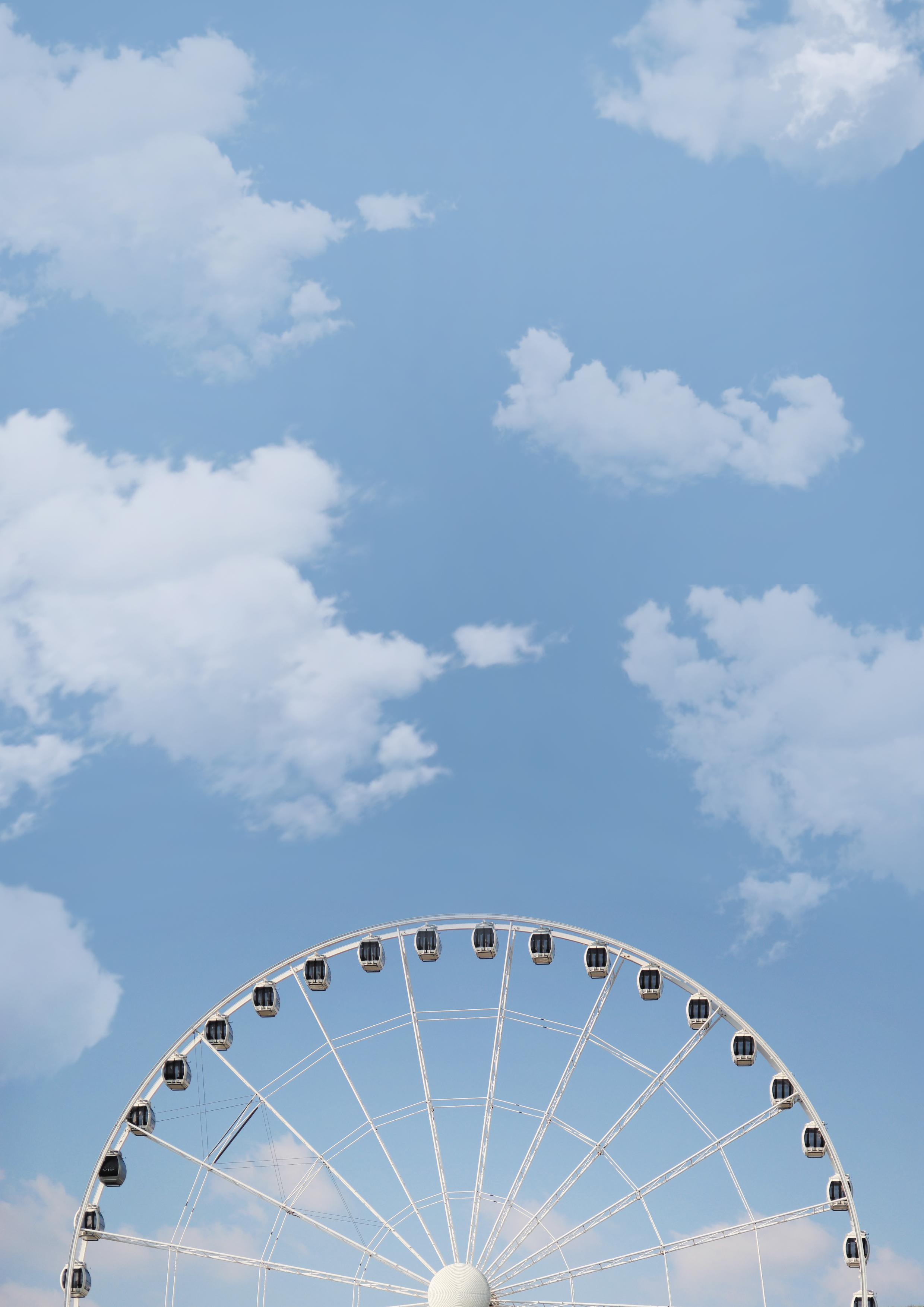 photo of white ferris wheel under white cloudy blue sky