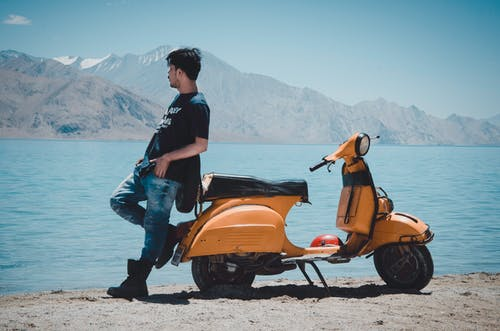 Photo of Man Leaning on Motorcycle