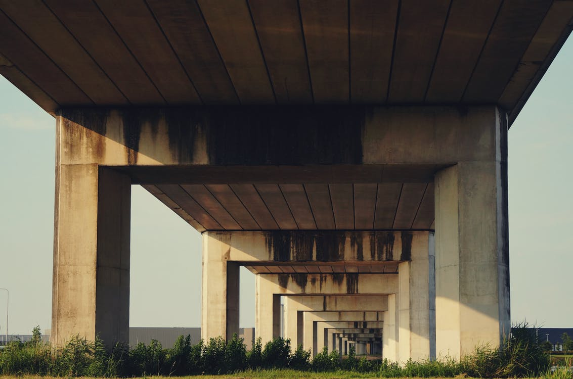 Green Grass Under Gray Concrete Elevated Highway