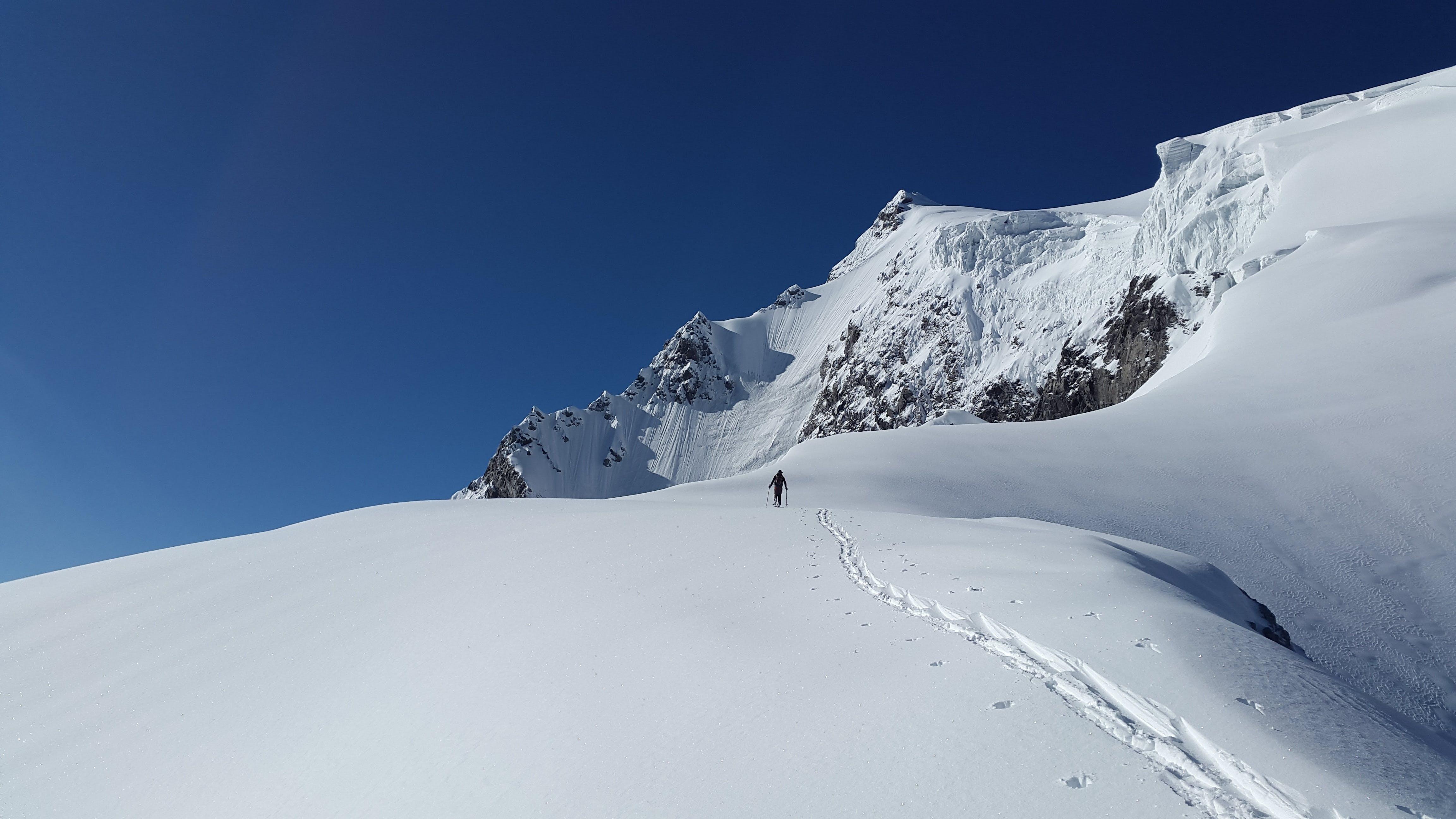 Man Walking in White Mountain Snow during Daytime
