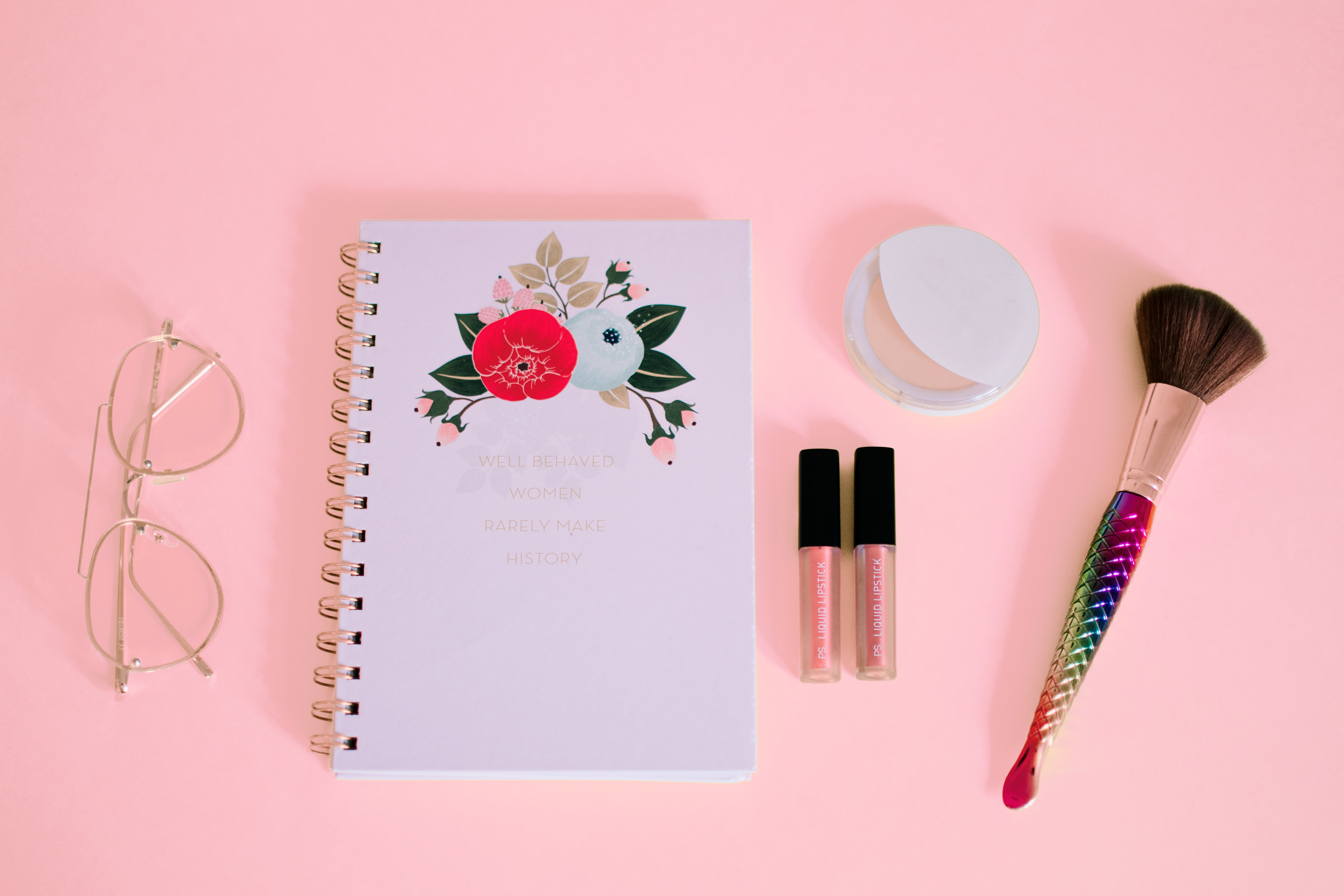 Flat lay Photography of Notebook Near Eyeglasses and Make-up