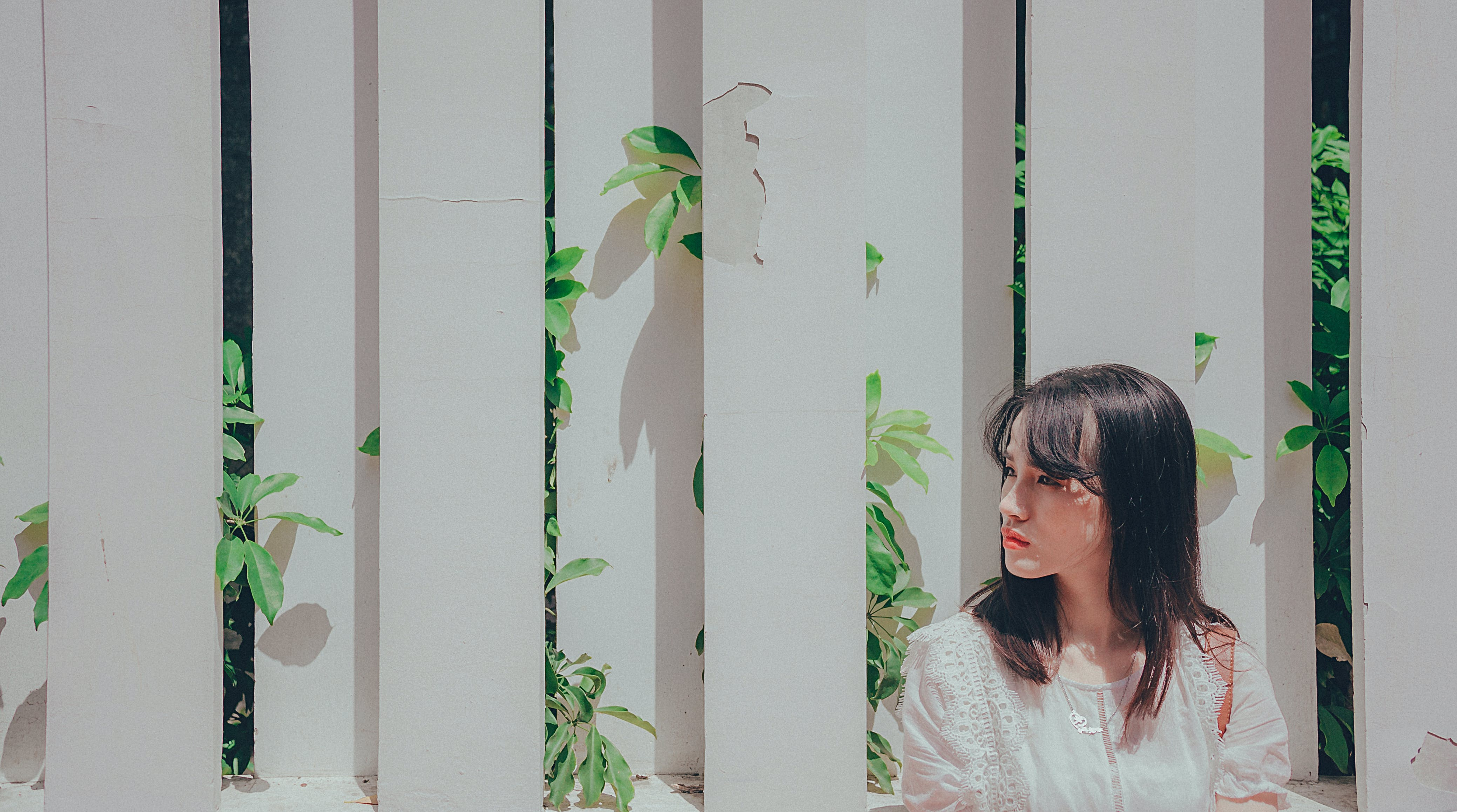 Woman Wearing White Shirt Leaning on White Wooden Fence With Plants