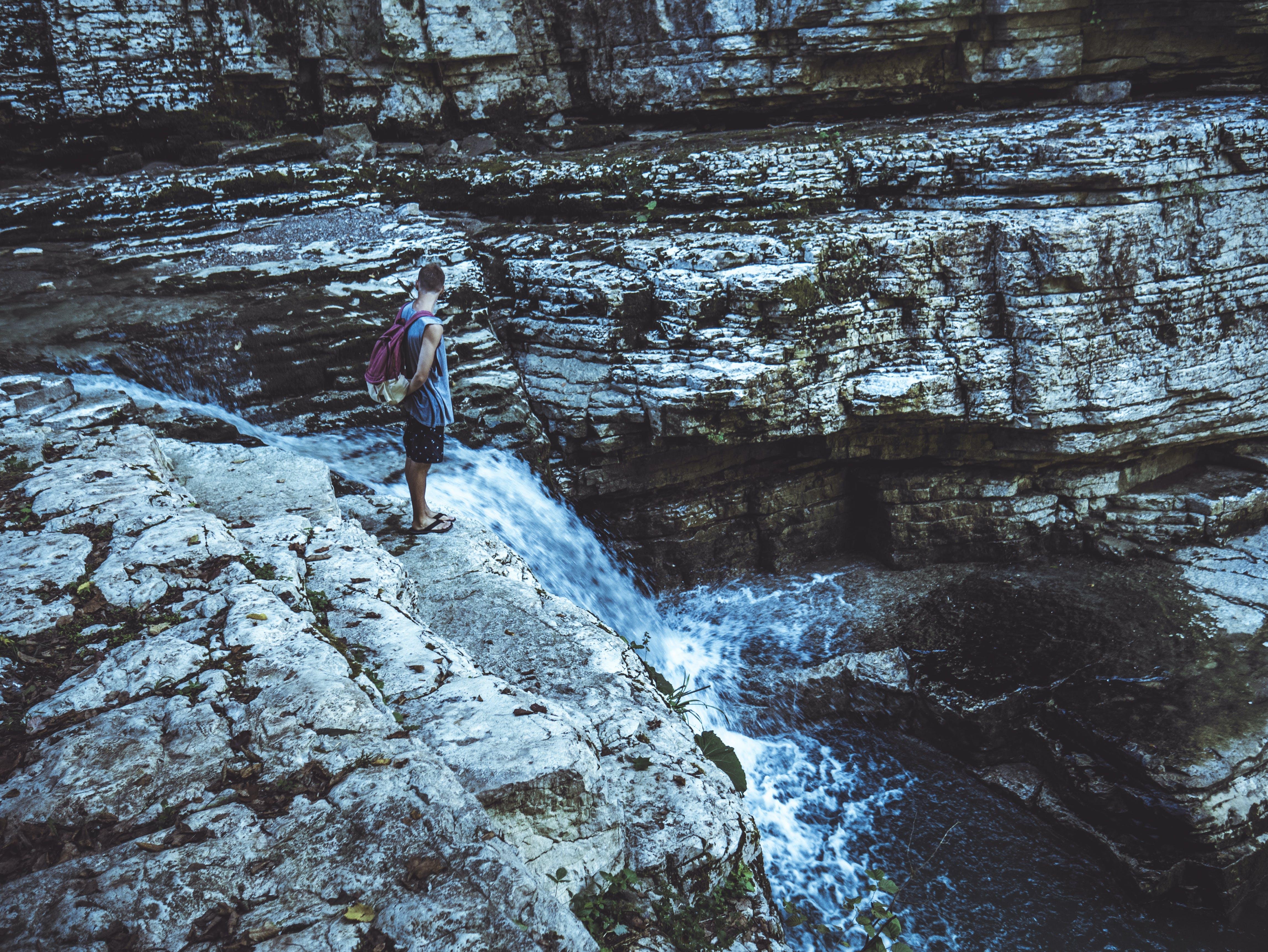 Man Standing in Waterfalls