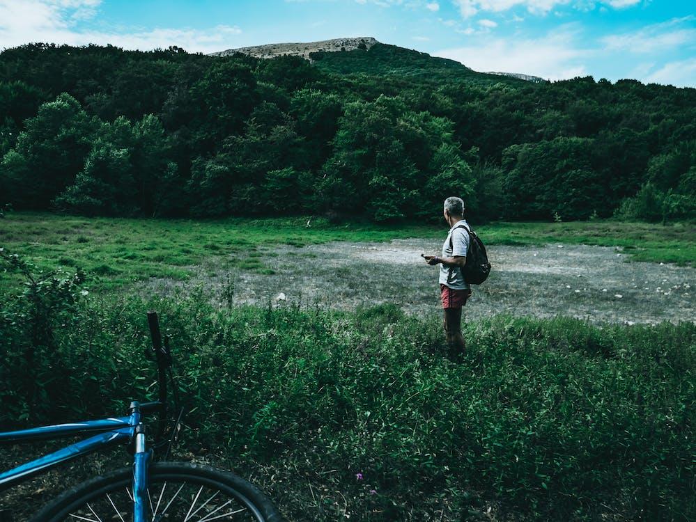 Man Wearing White Shirt Standing on Green Grass Field