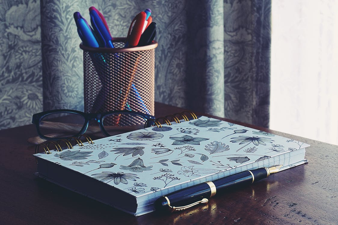 Close-Up Photography of Notebook Near Pens