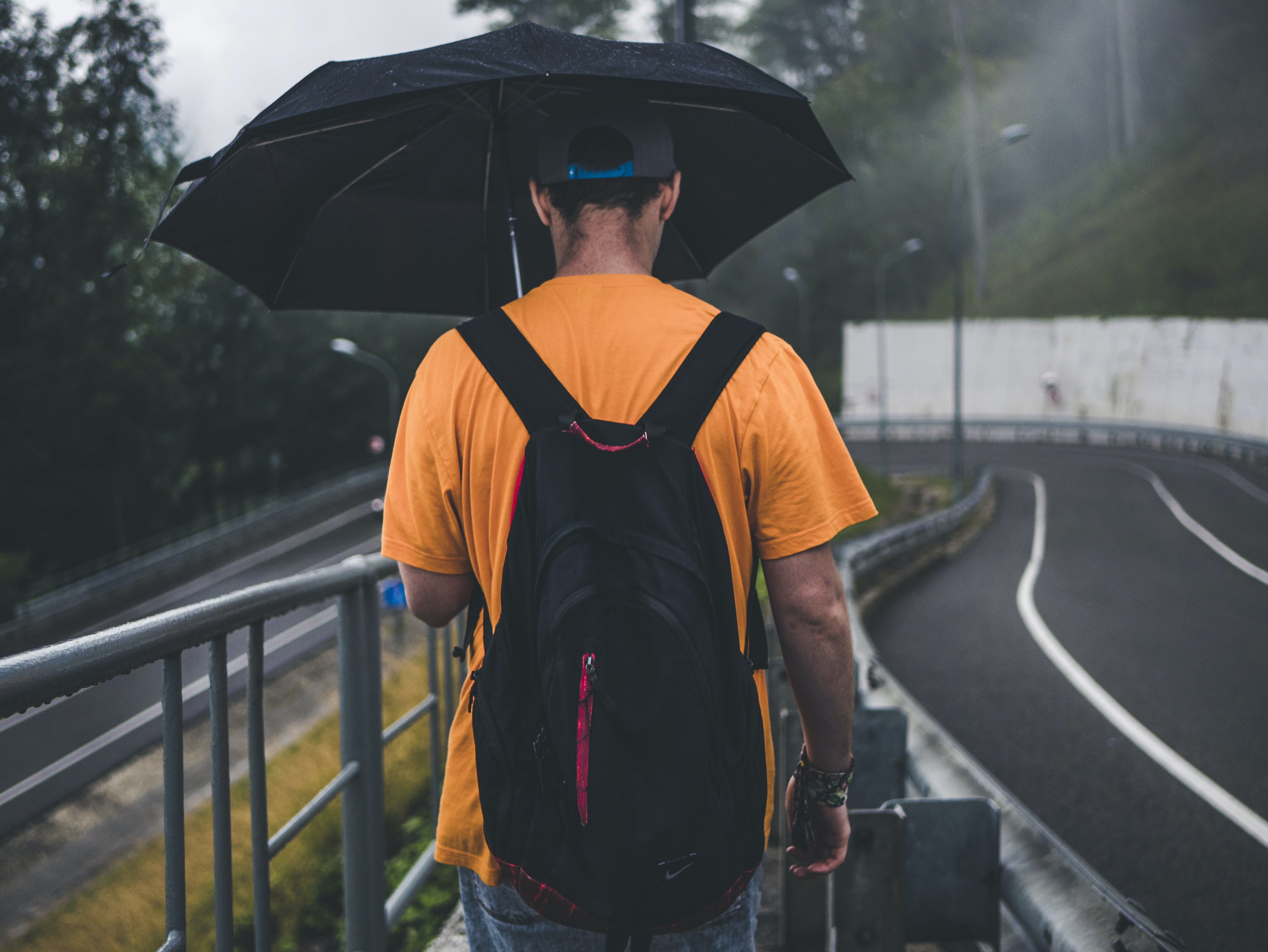Man Wearing Orange Shirt Holding Black Umbrella