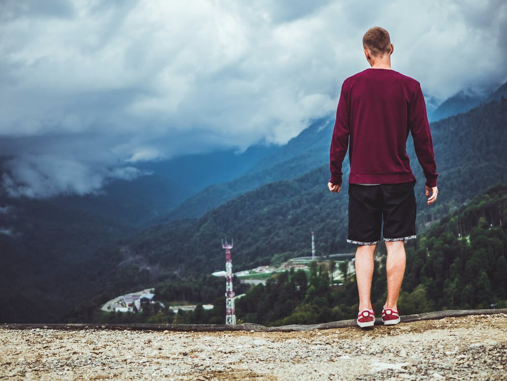 Man Wearing Maroon Sweater and Black Shorts Standing in Front of Mountain