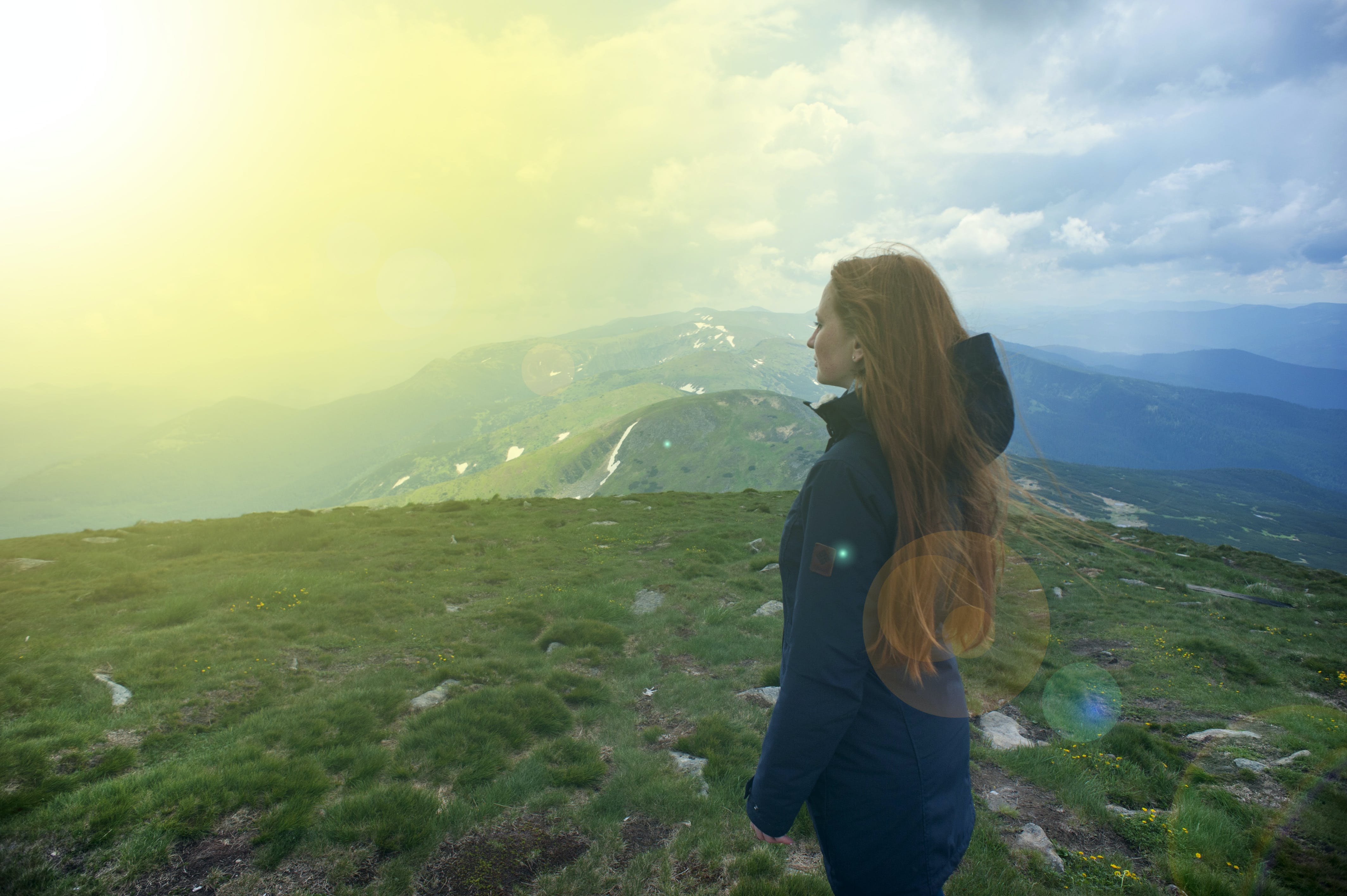 Photography of Woman On Top of Mountain