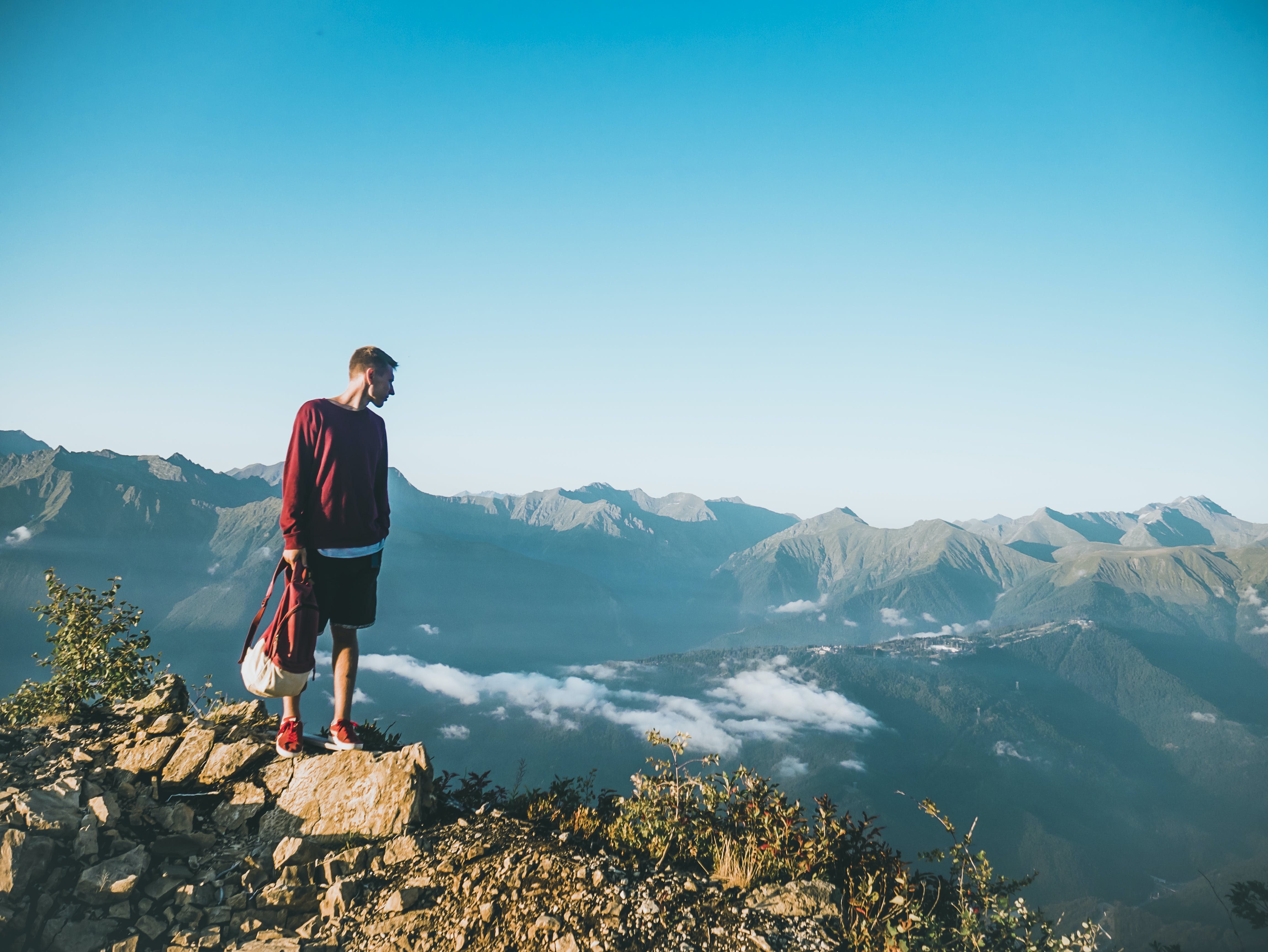 Man in Red Sweatshirt and Black Shorts Standing on Large Brown Rock on Top of a Mountain