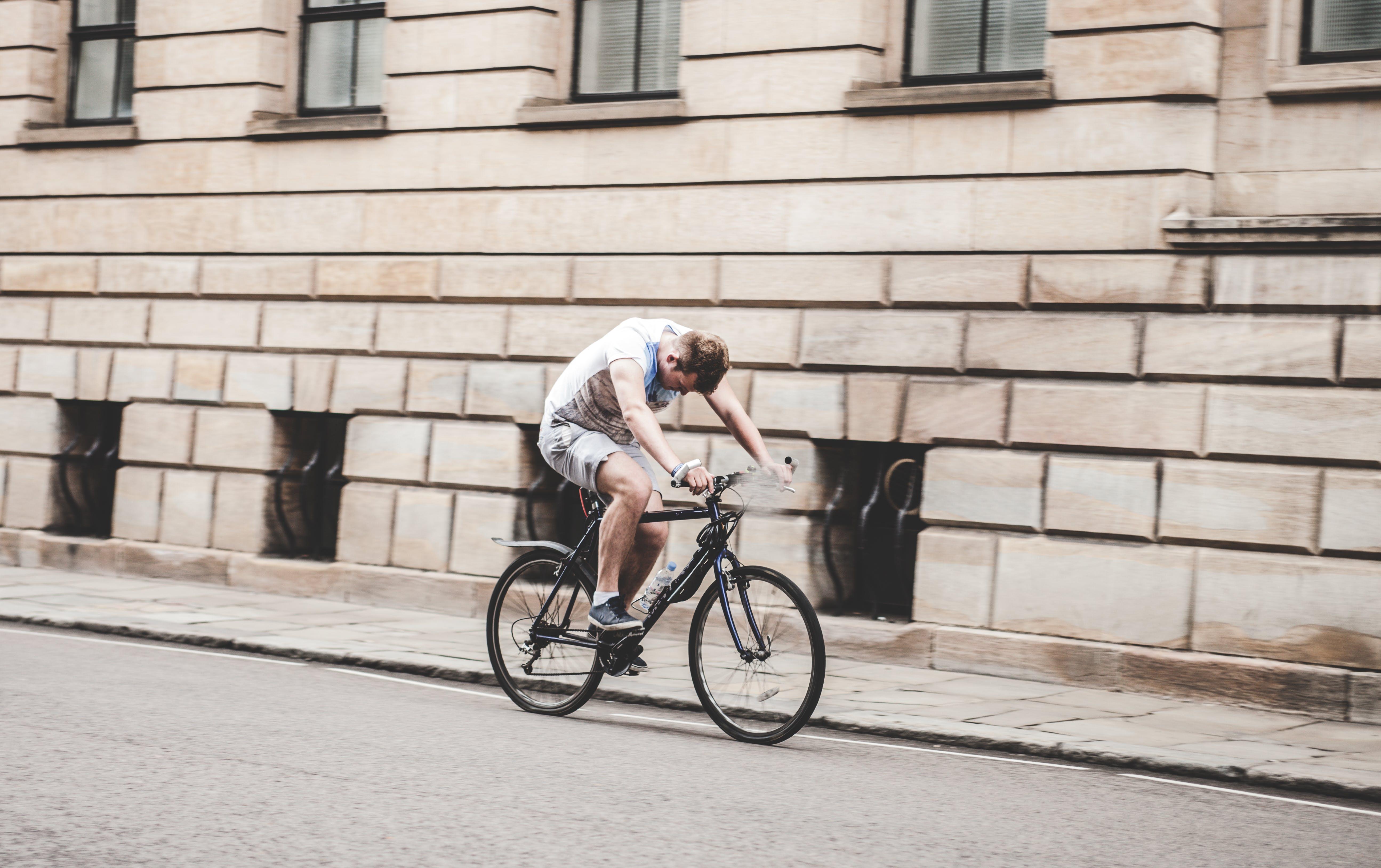 Man Riding Black Mountain Bike on Pathway during Daytime