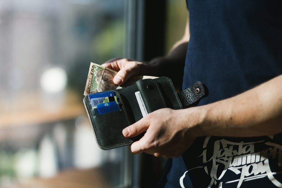 Photograph of Person Holding Black Leather Wallet with Money