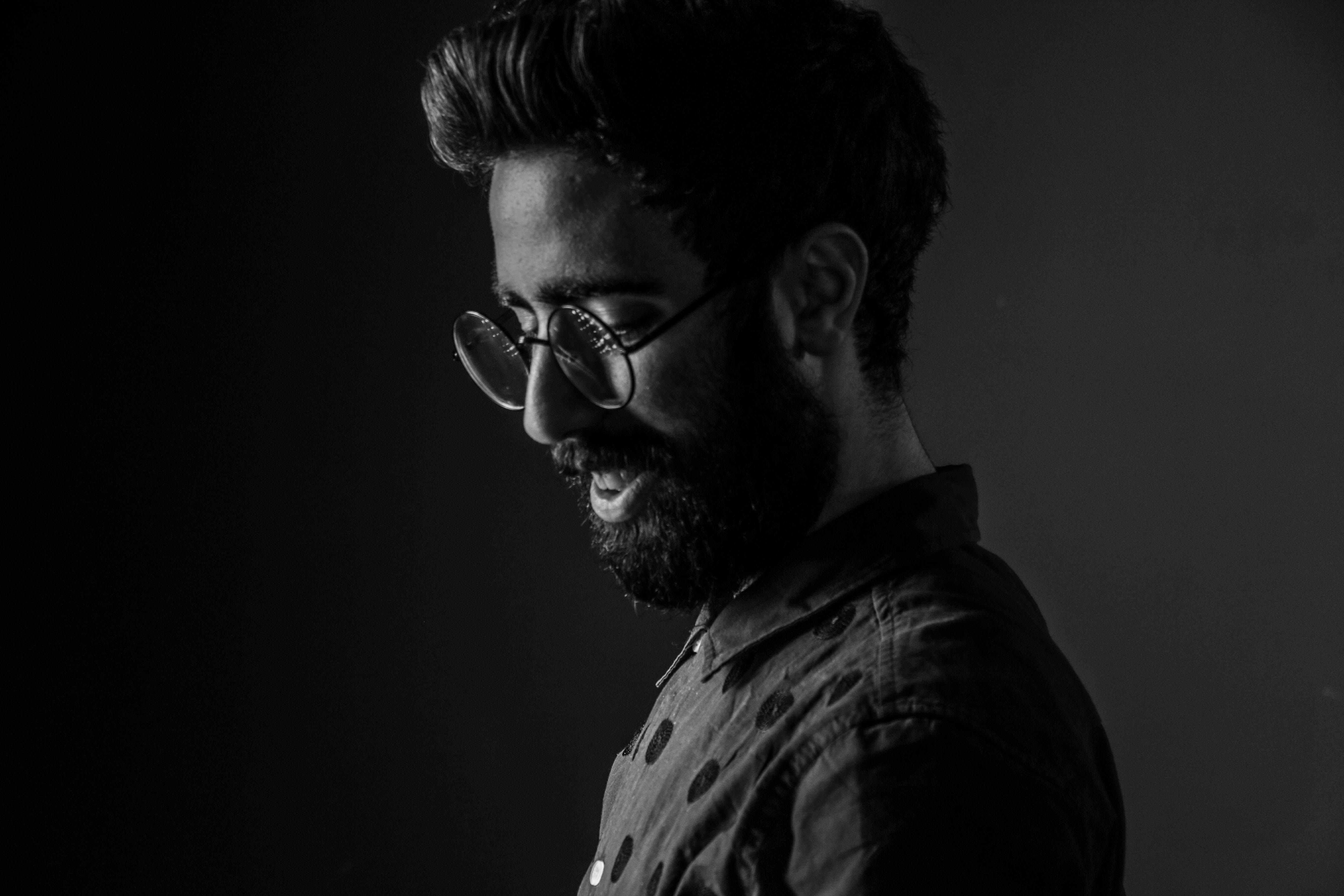Grayscale Photography of Man Wearing Round Eyeglasses