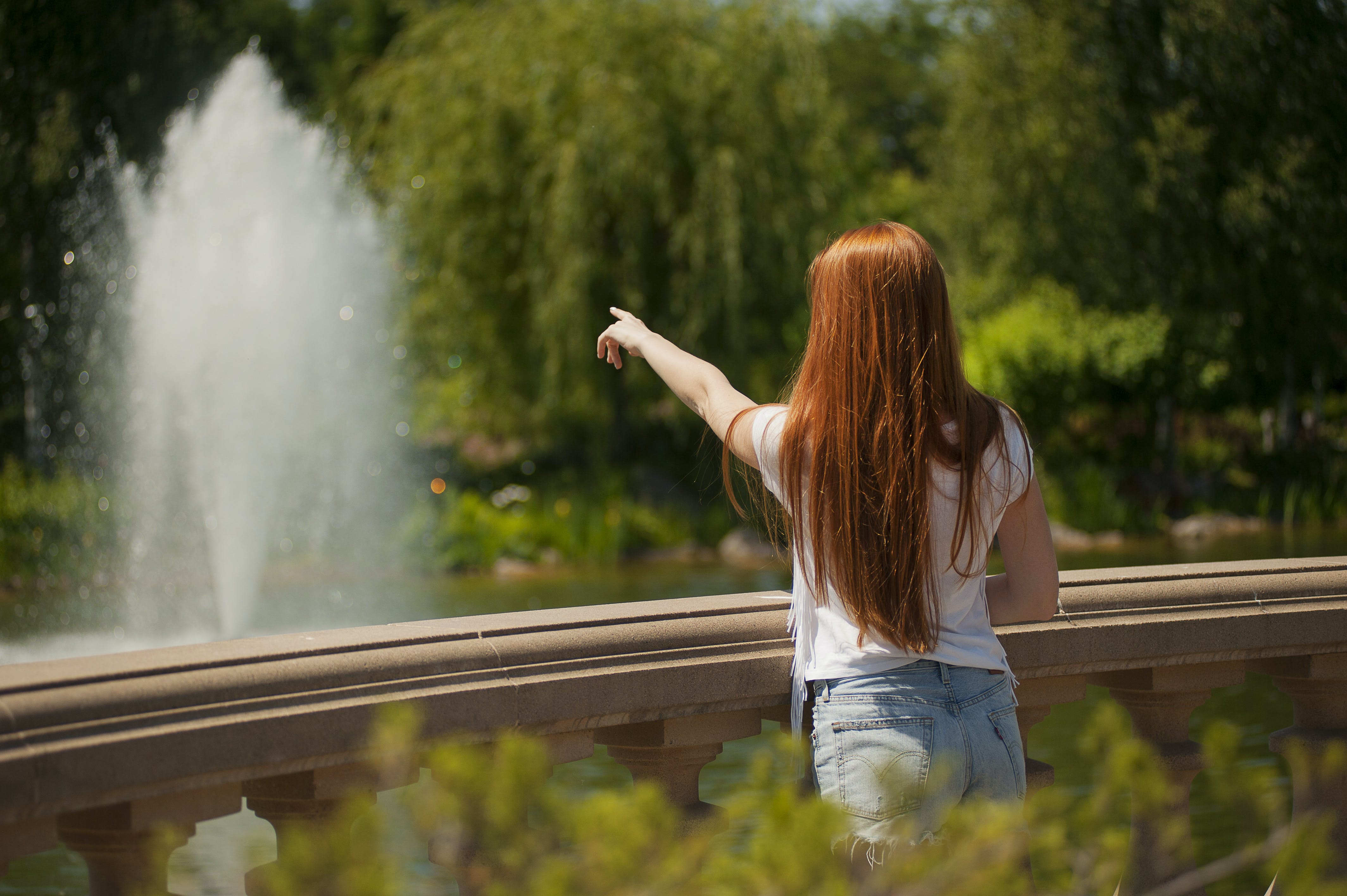 Shallow Focus Photo of Woman Standing in Front of Body of Water With Fountain