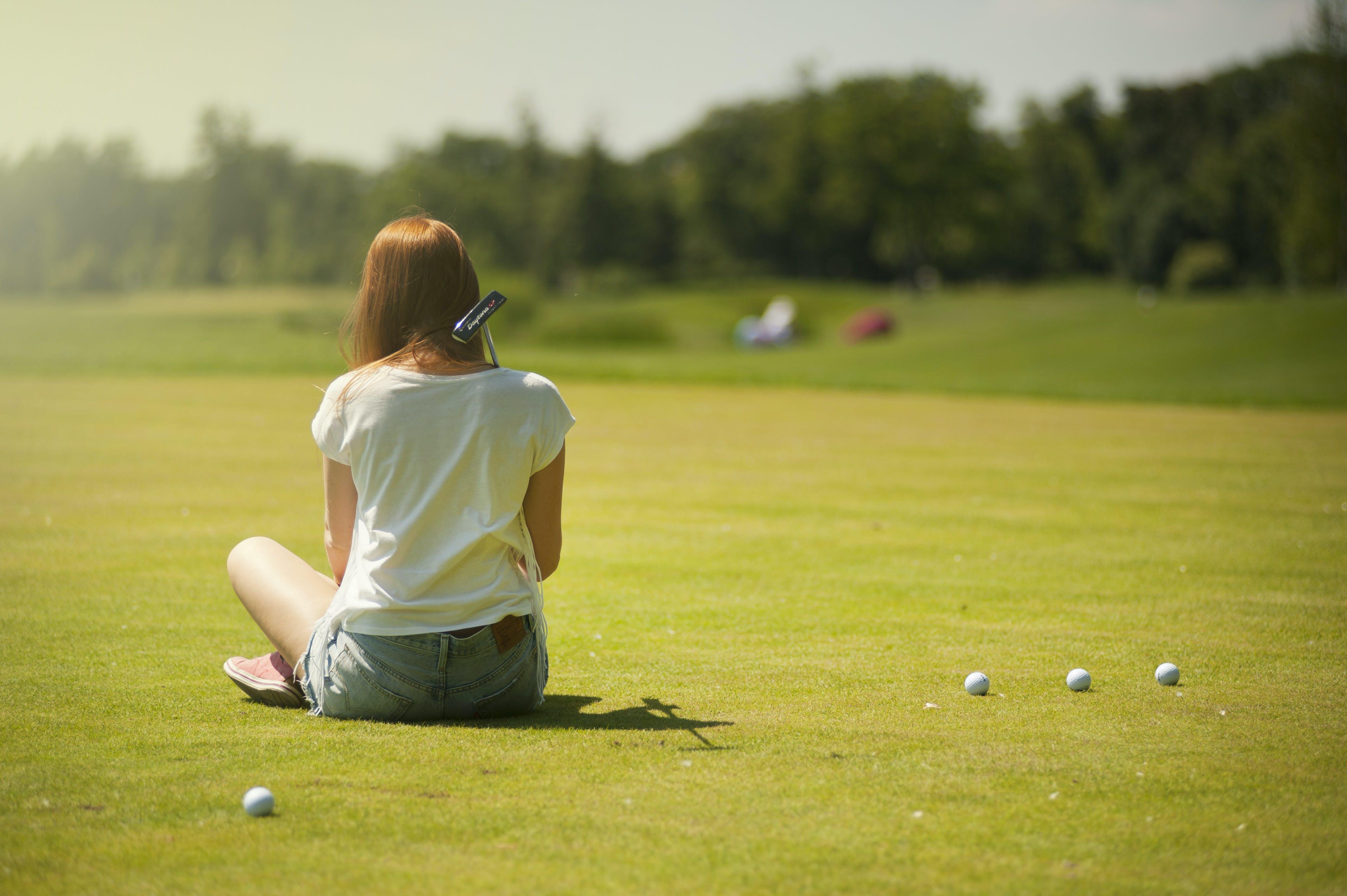 Photo of Woman Sitting on Grass Field