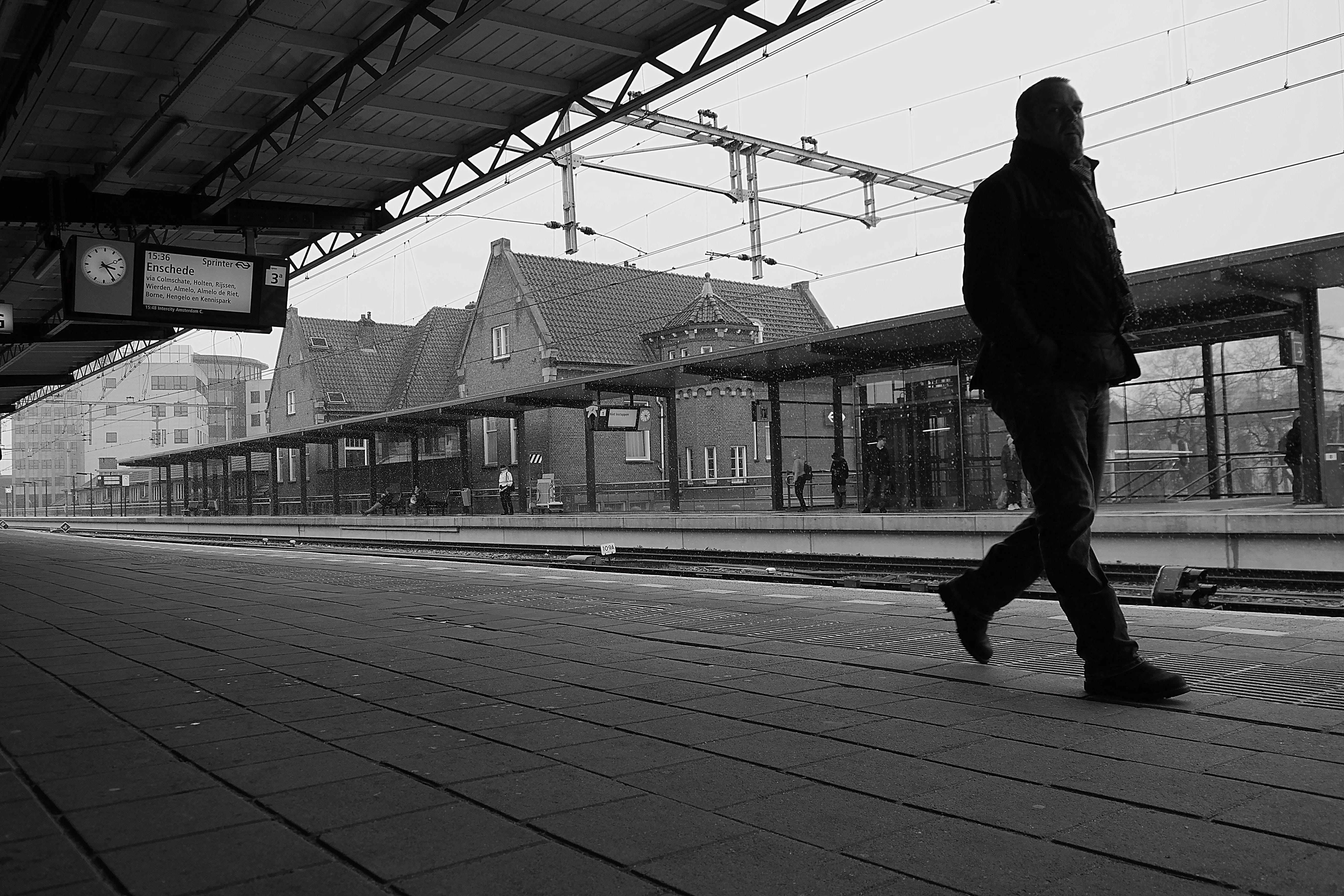 Grayscale Photo of Man Walking on Train Platform
