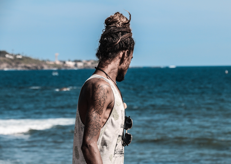 Man in White Tank Top on Seashore