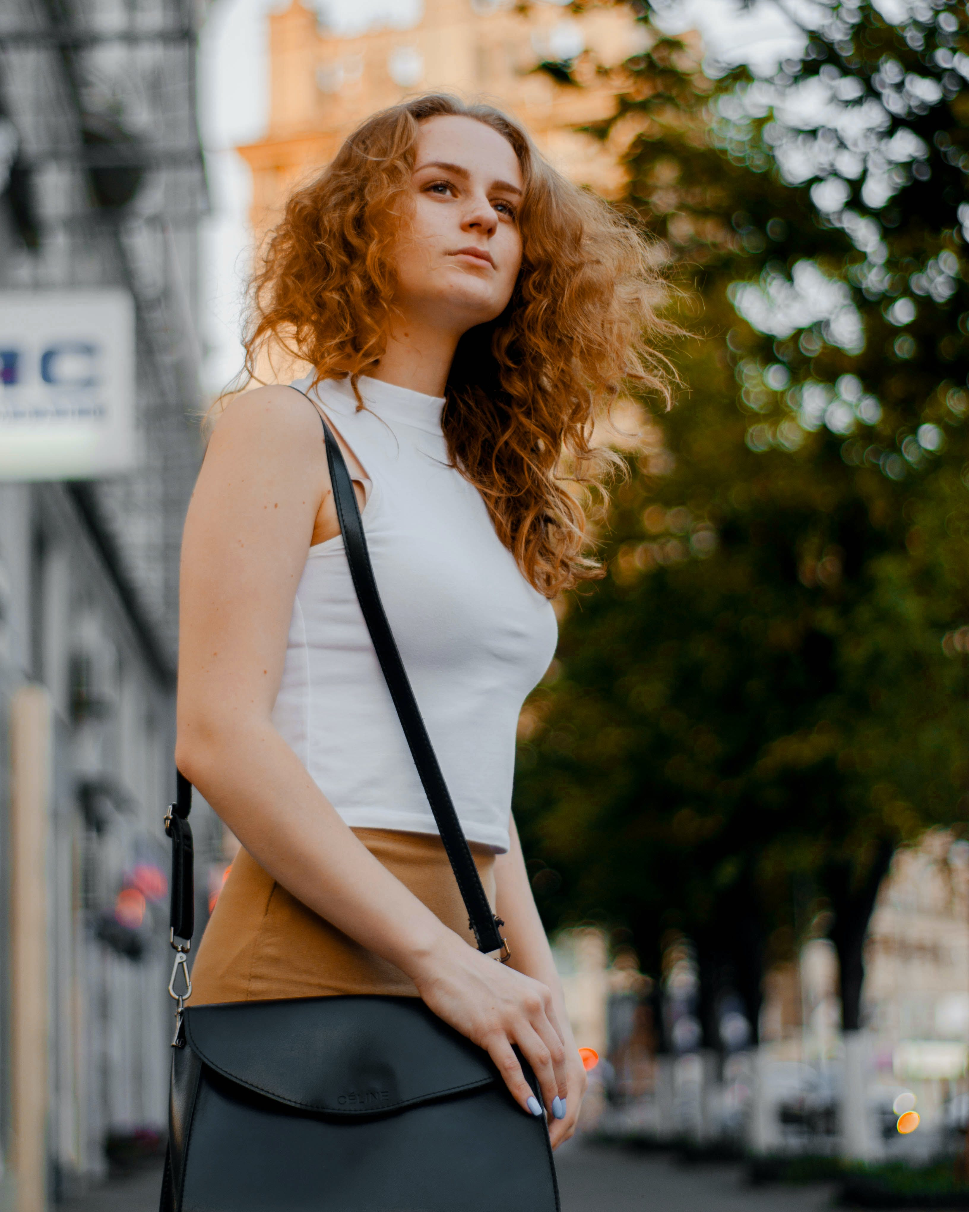 Woman in White Turtleneck Sleeveless Top and Brown Bottoms Holding Black Leather Crossbody Bag Outfit