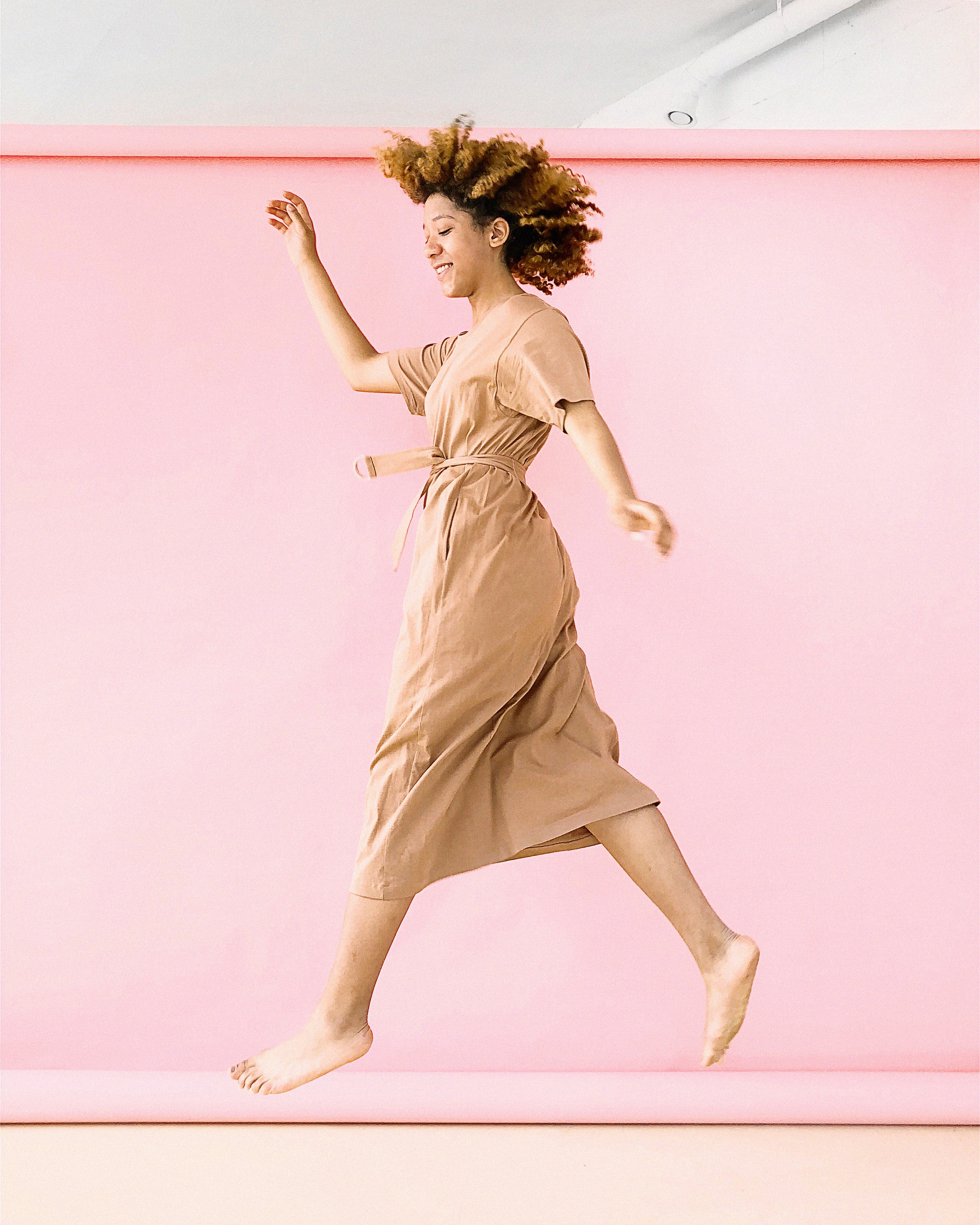 Woman Wearing Brown Dress Jump Near Pink Wall