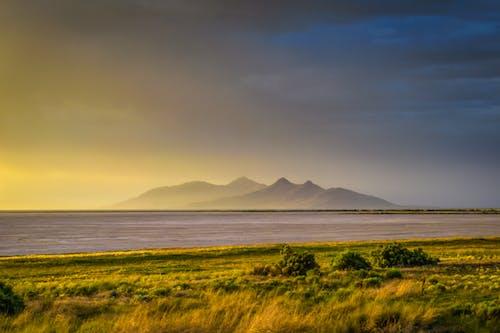 Kostnadsfri bild av berg, fält, gyllene timmen, kustlinje