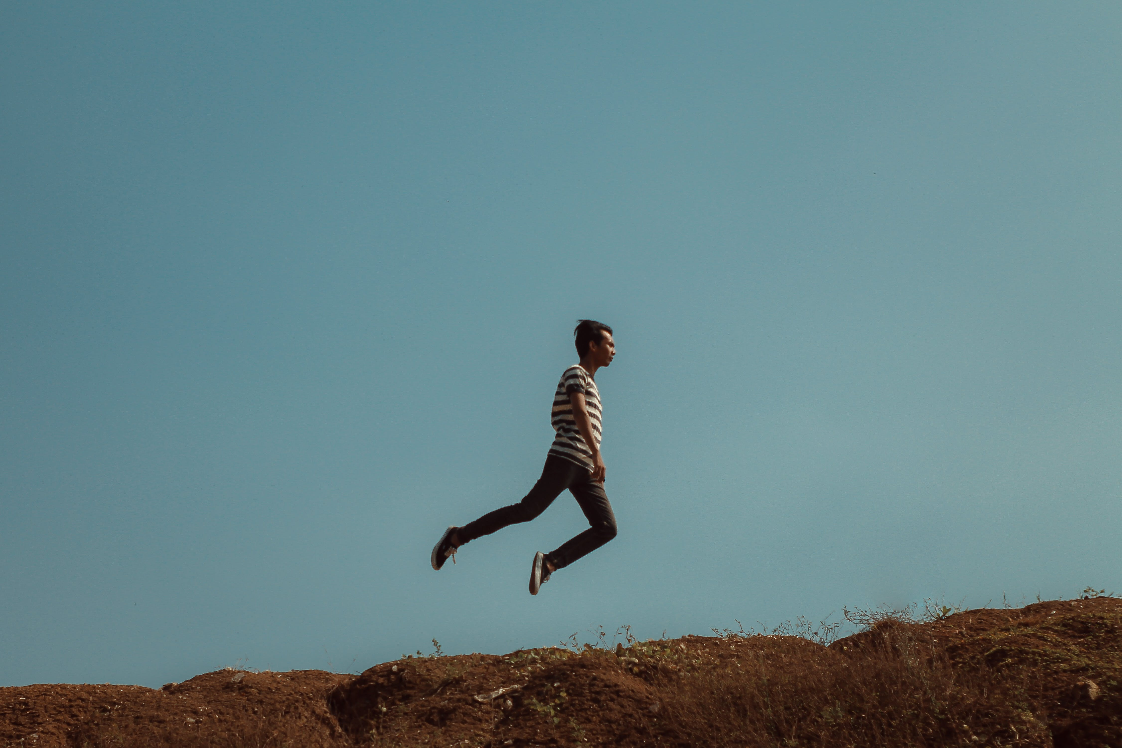 Man Jumping Near the Cliff
