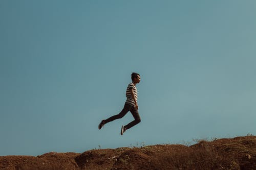Man Jumping Near the Cliff