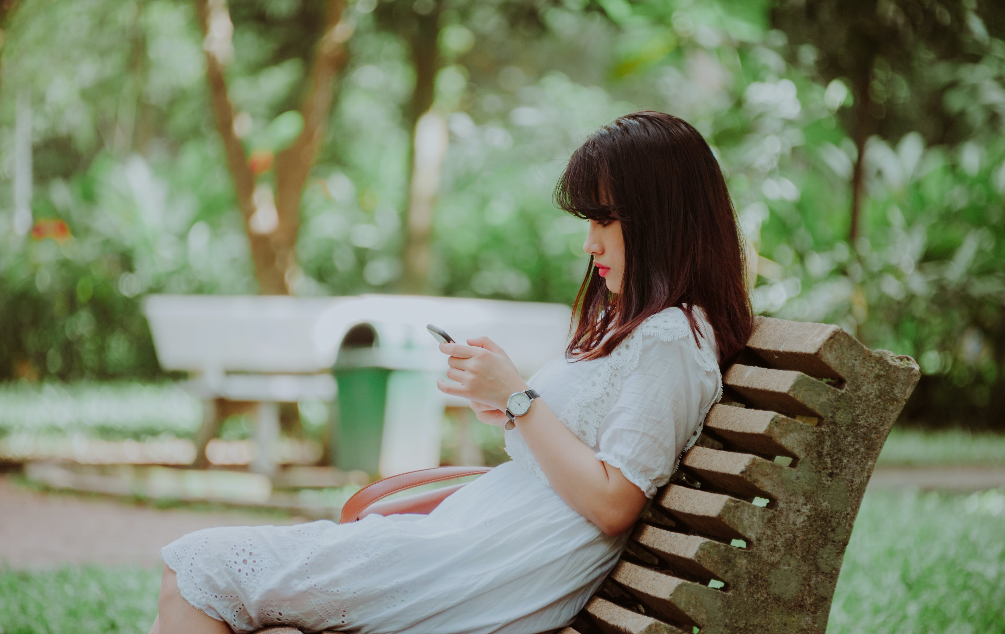 Woman Sitting on Bench Checking Her Phone