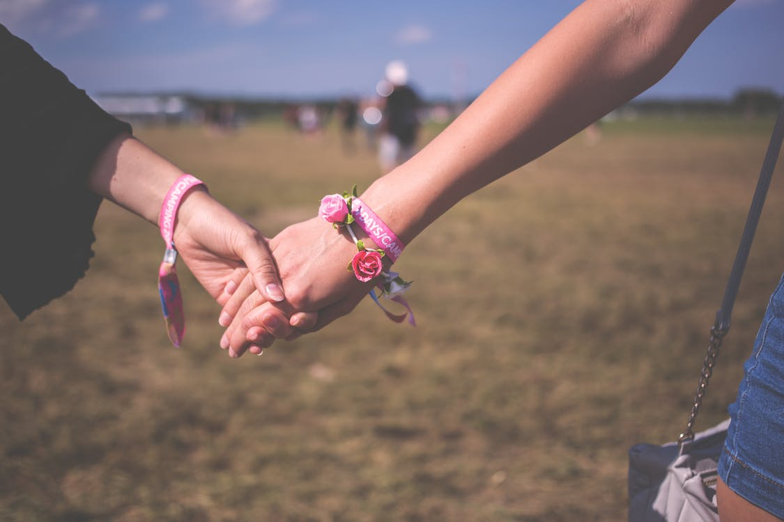 2 Person Holding Each Other Wearing Pink Friendship Bracelet during Daytime