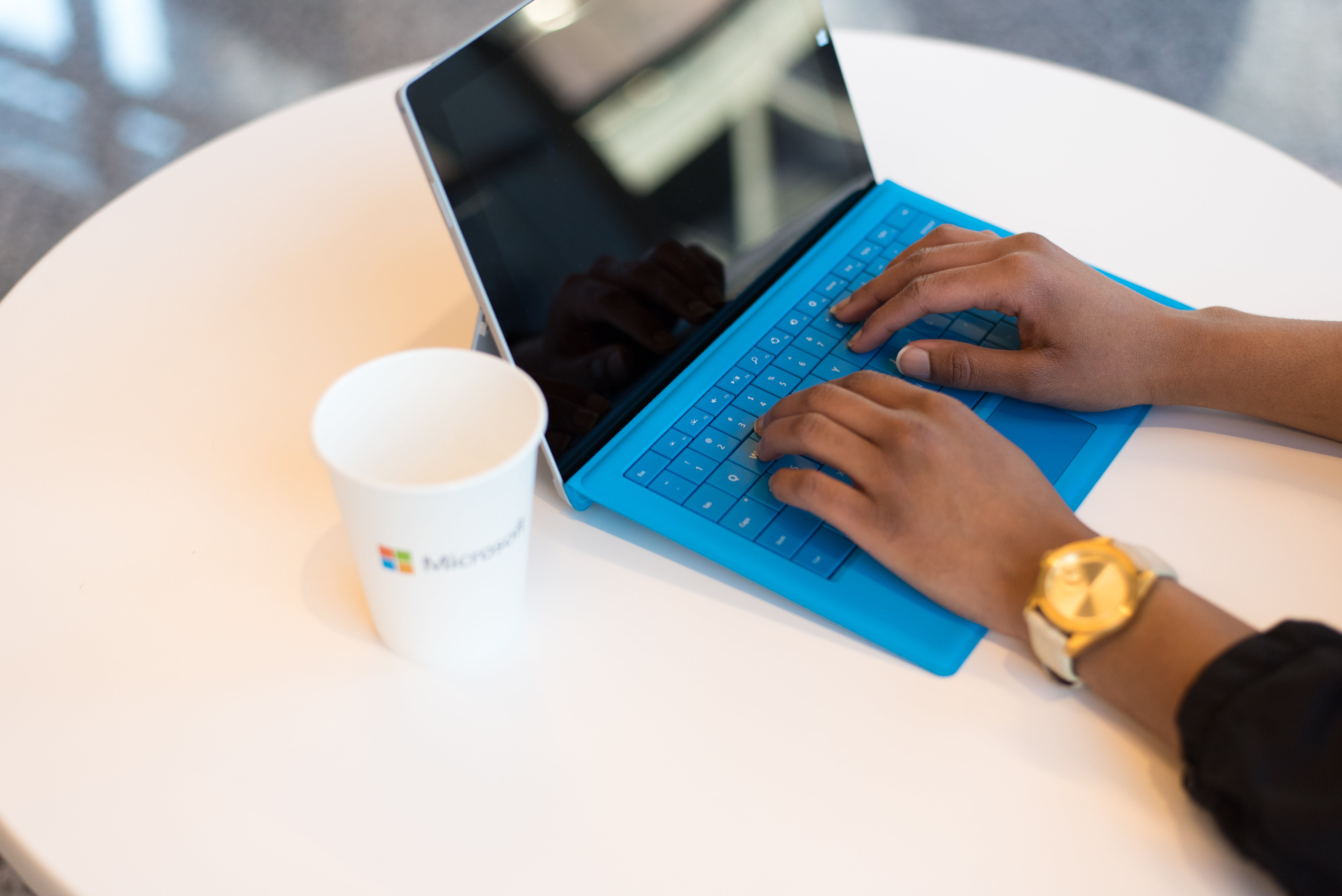 Person Wearing Round Gold-colored Watch Using Black Tablet Computer With Blue Detachable Keyboard on Round White Wooden Table
